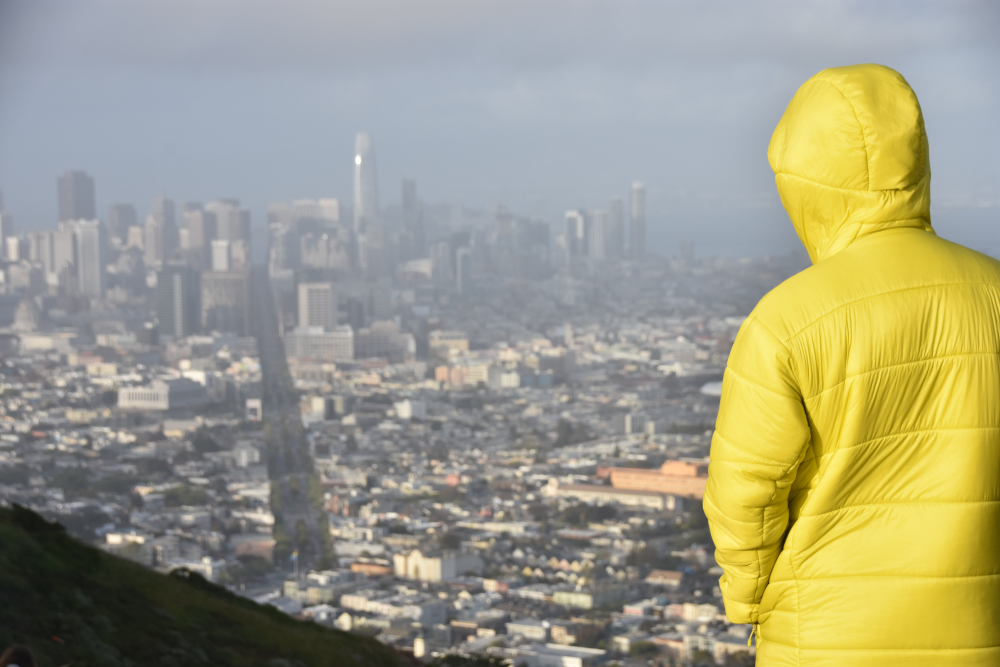 A man in a yellow jacket looking over a foggy SF skyline.