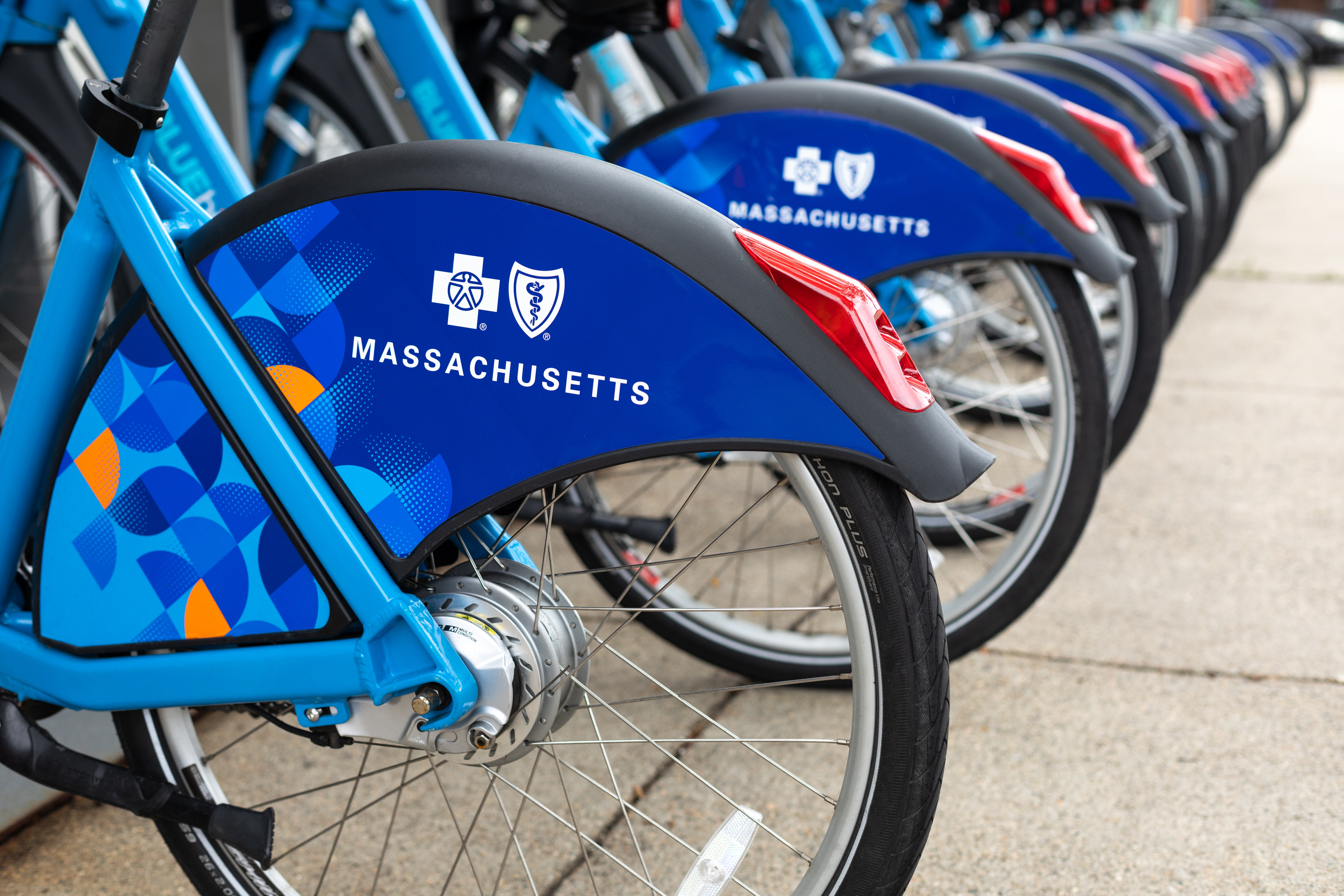 A row of identical-looking bikes parked a bike-share kiosk on a city sidewalk.