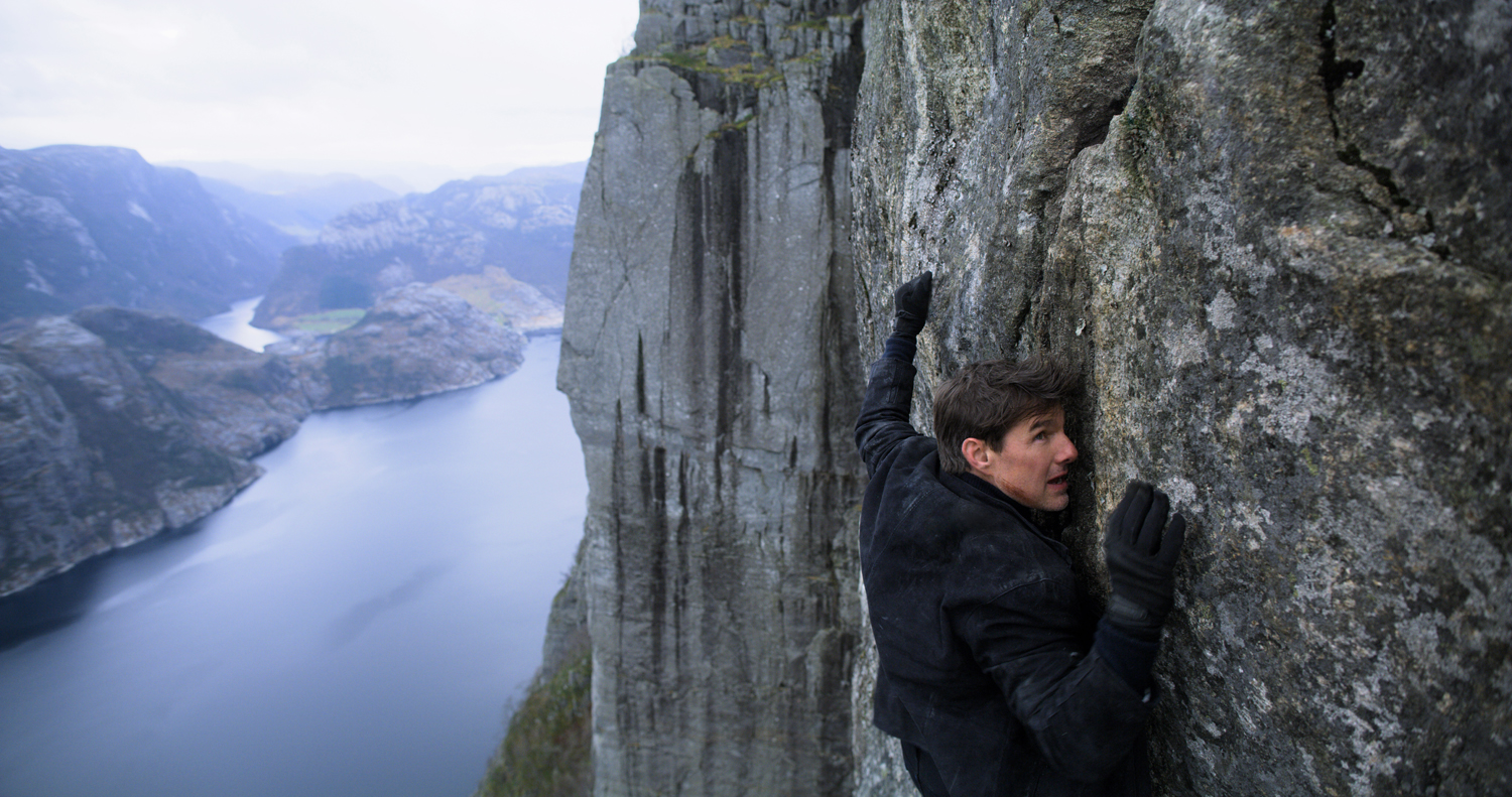 Tom Cruise hangs from a cliff in Mission: Impossible — Fallout.