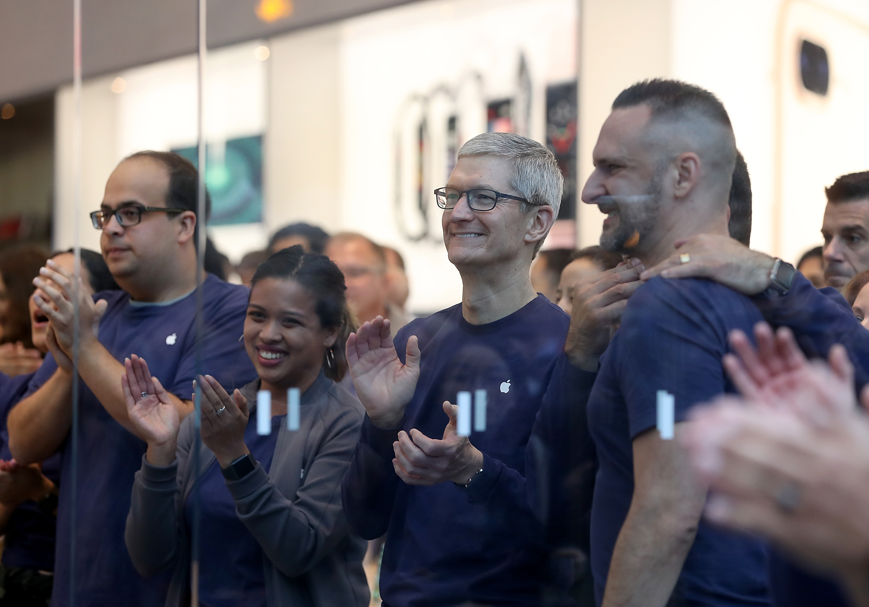 Apple CEO Tim Cook applauds at an Apple Store event