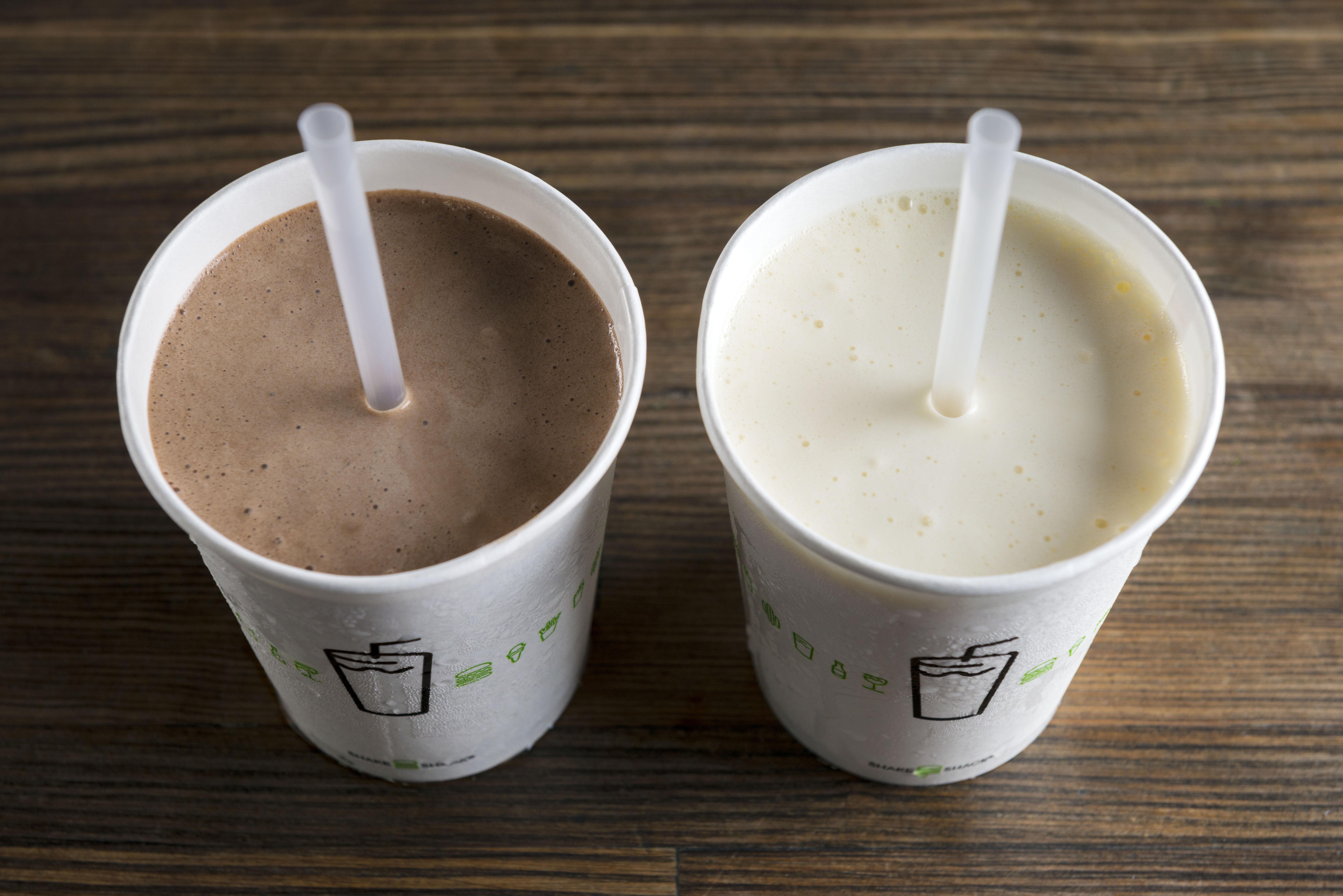 Two shake shack milkshakes with plastic straws