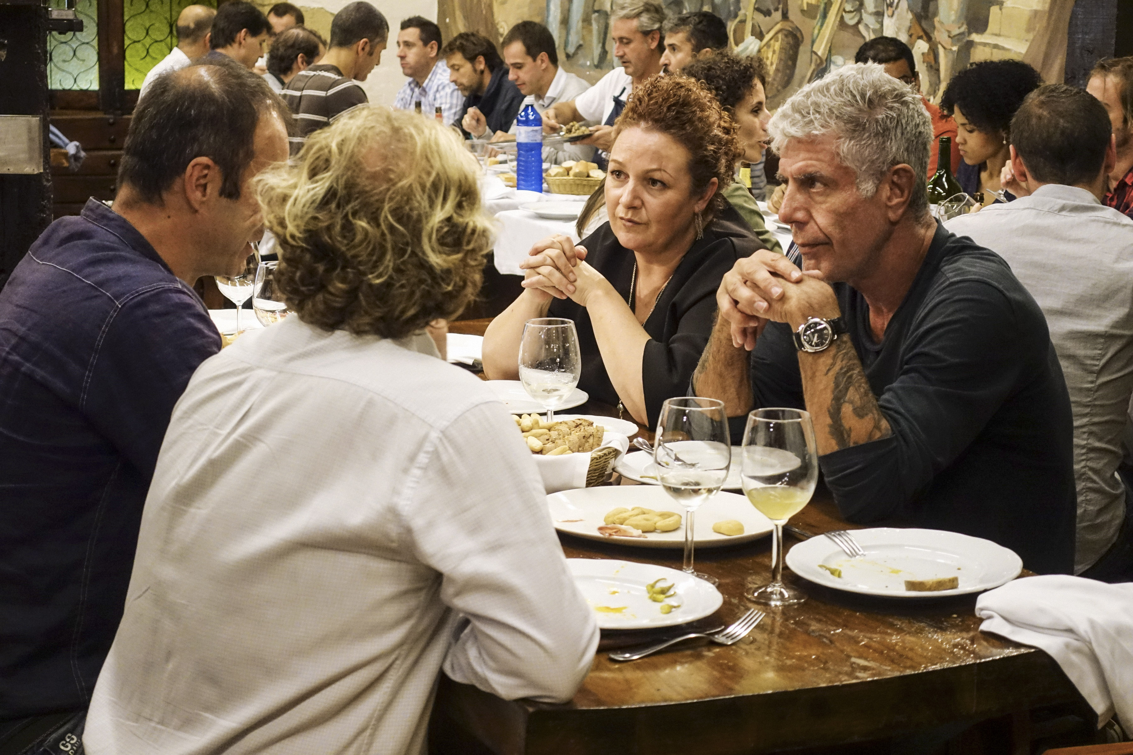 Anthony Bourdain and guests sit around a table during the San Sebastian episode of 'Parts Unknown.'