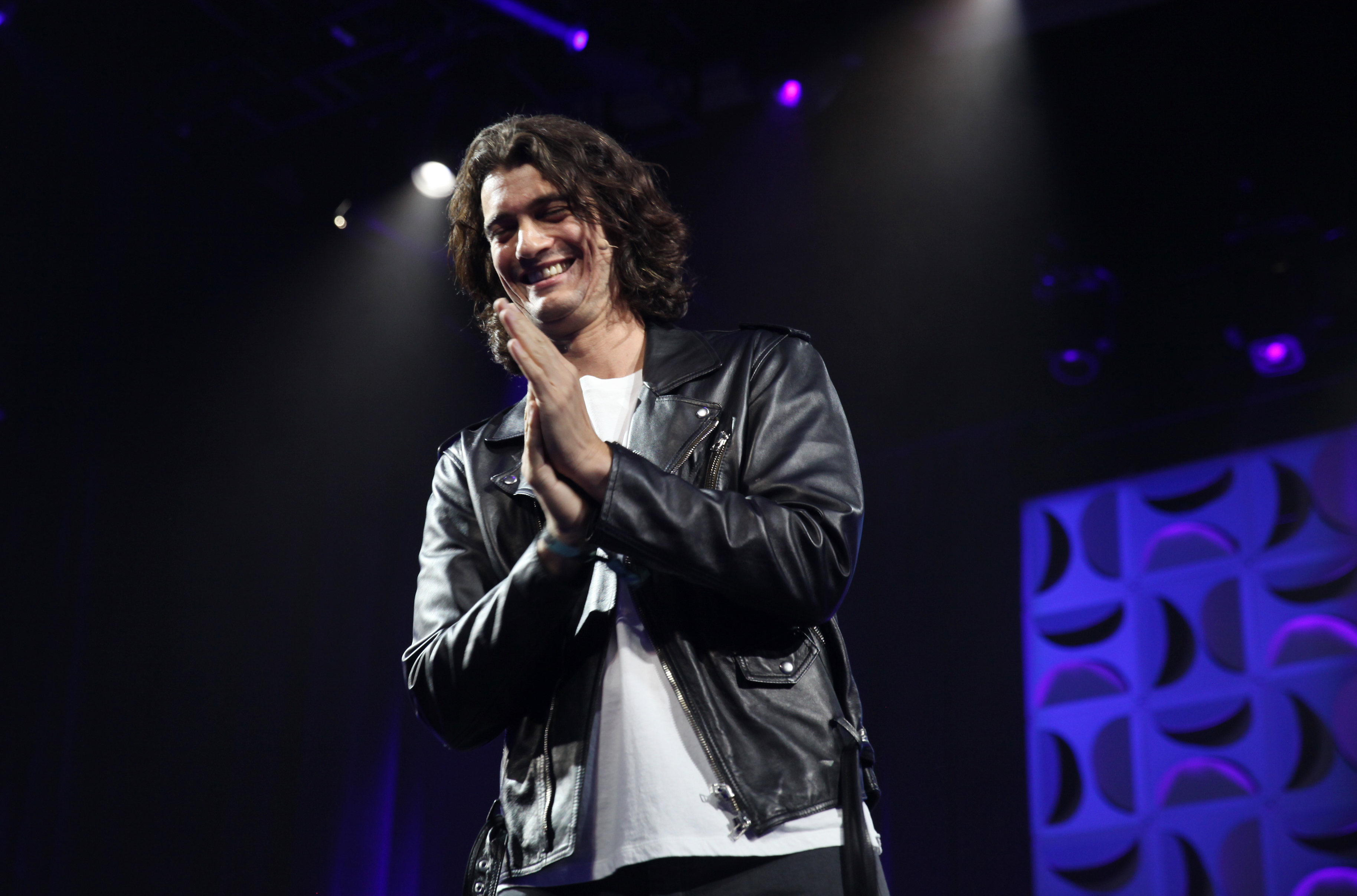 WeWork's ex-CEO Adam Neumann clasps his hands and smiles at the audience from onstage.