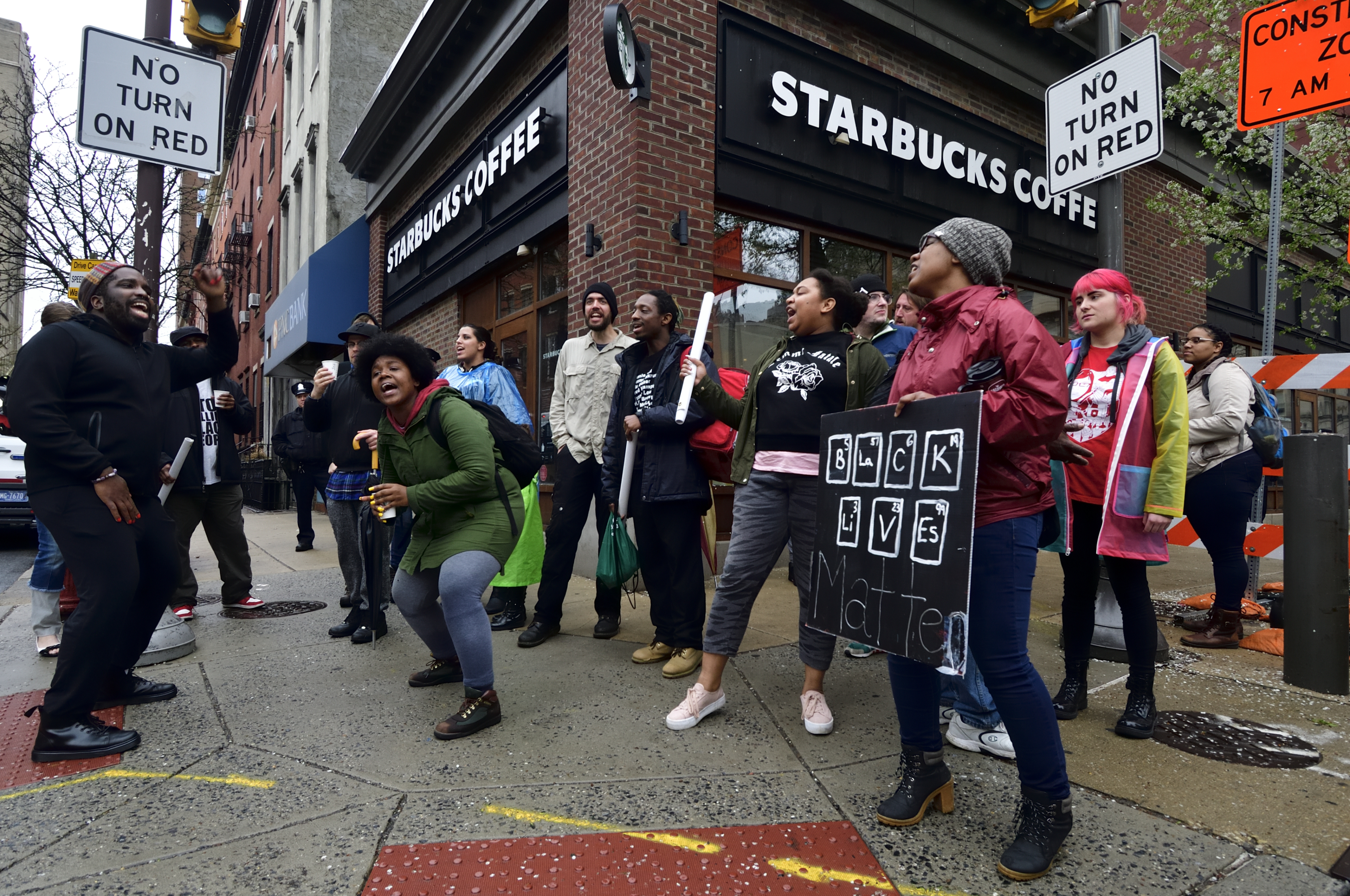 Protesters march past the Starbucks in Philadelphia's Center City, where two black men were arrested for loitering