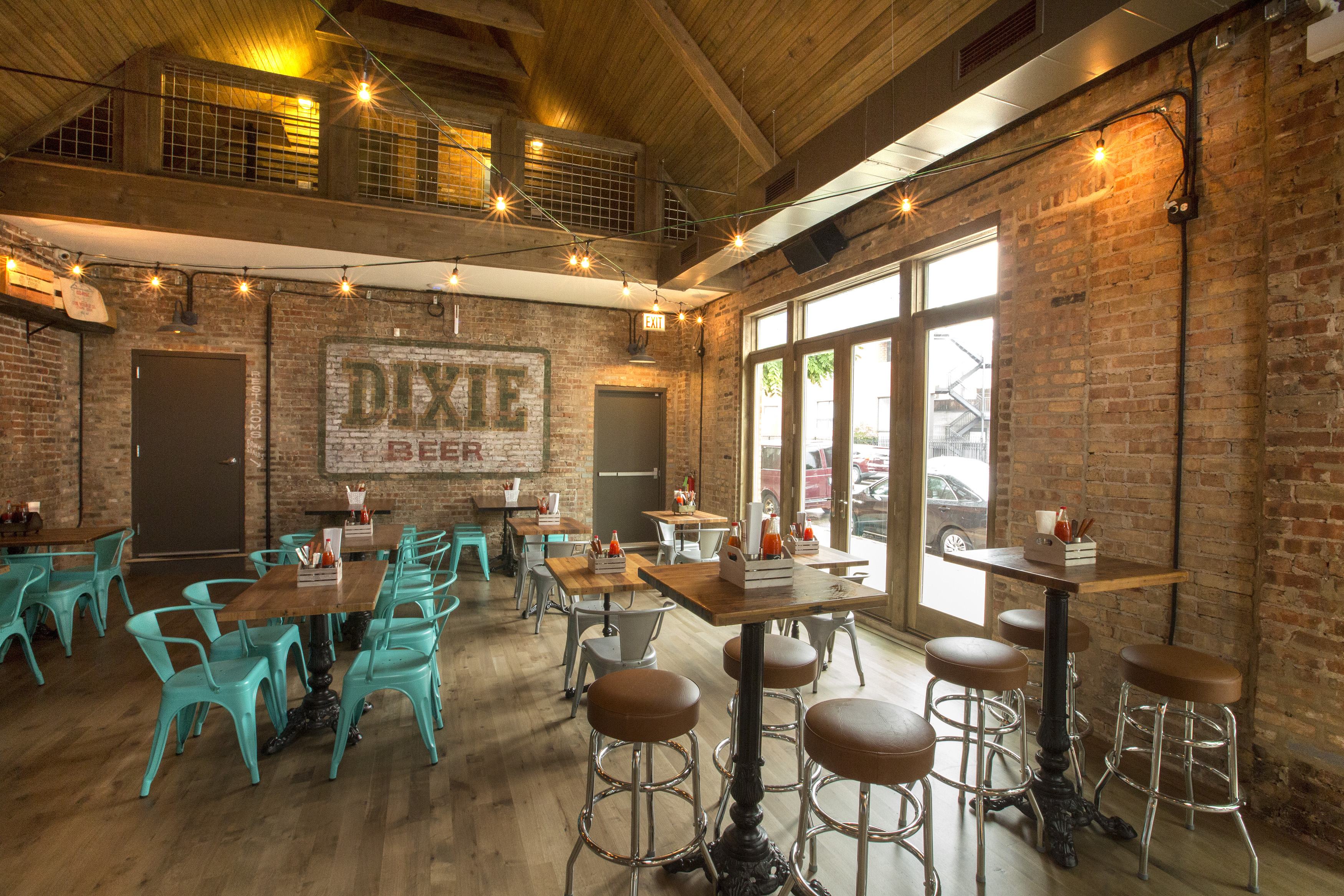 A restaurant with exposed brick walls with vintage seating and stools.