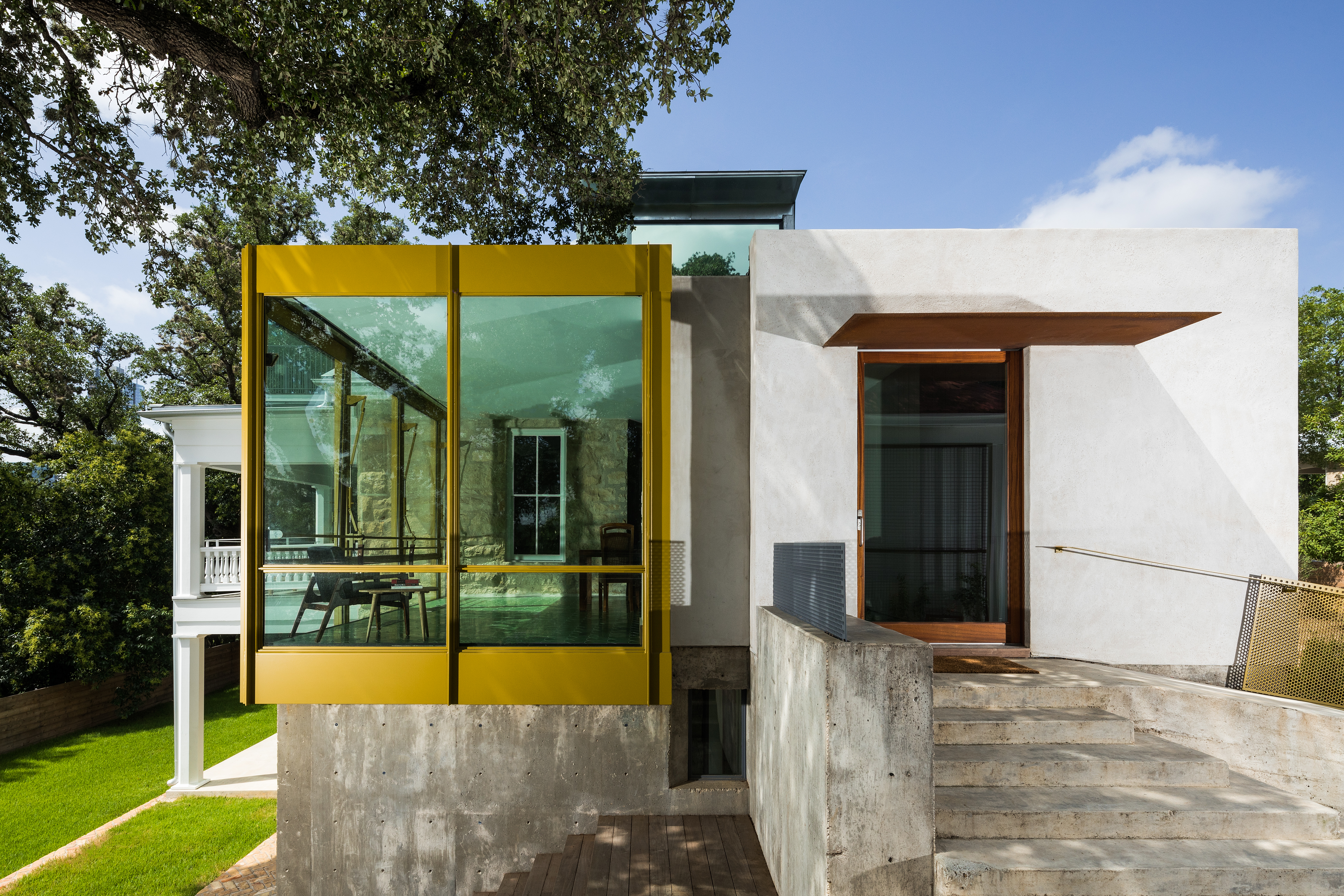 A split level traditional stone house with a very contemporary yellow and white addition in front
