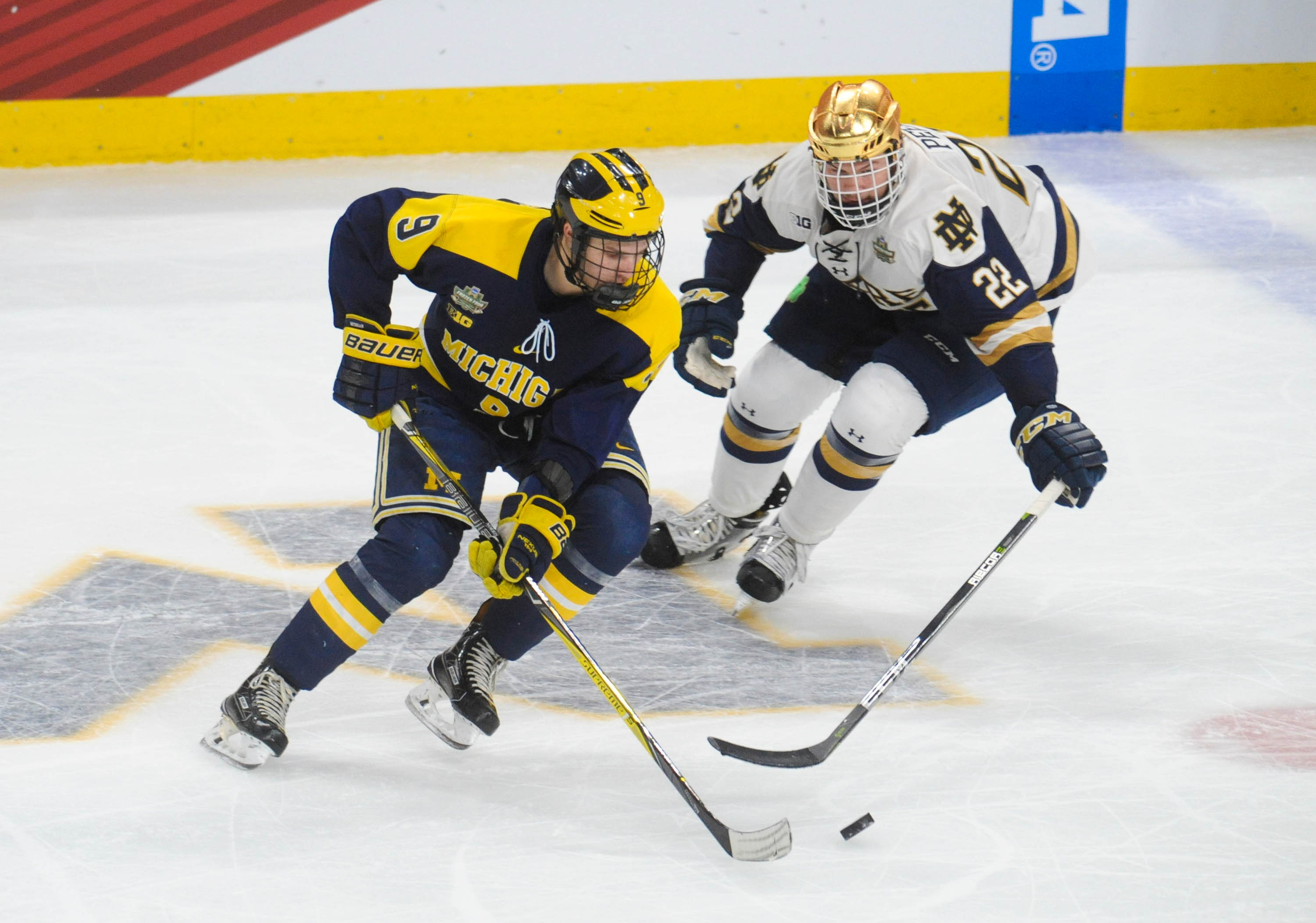 Apr 5, 2018; St. Paul, MN, USA; Michigan forwards Josh Norris (9) and Notre Dame defenseman Andrew Peeke (22) chase the puck at center ice during the second period in the 2018 Frozen Four college hockey national semifinals at Xcel Energy Center