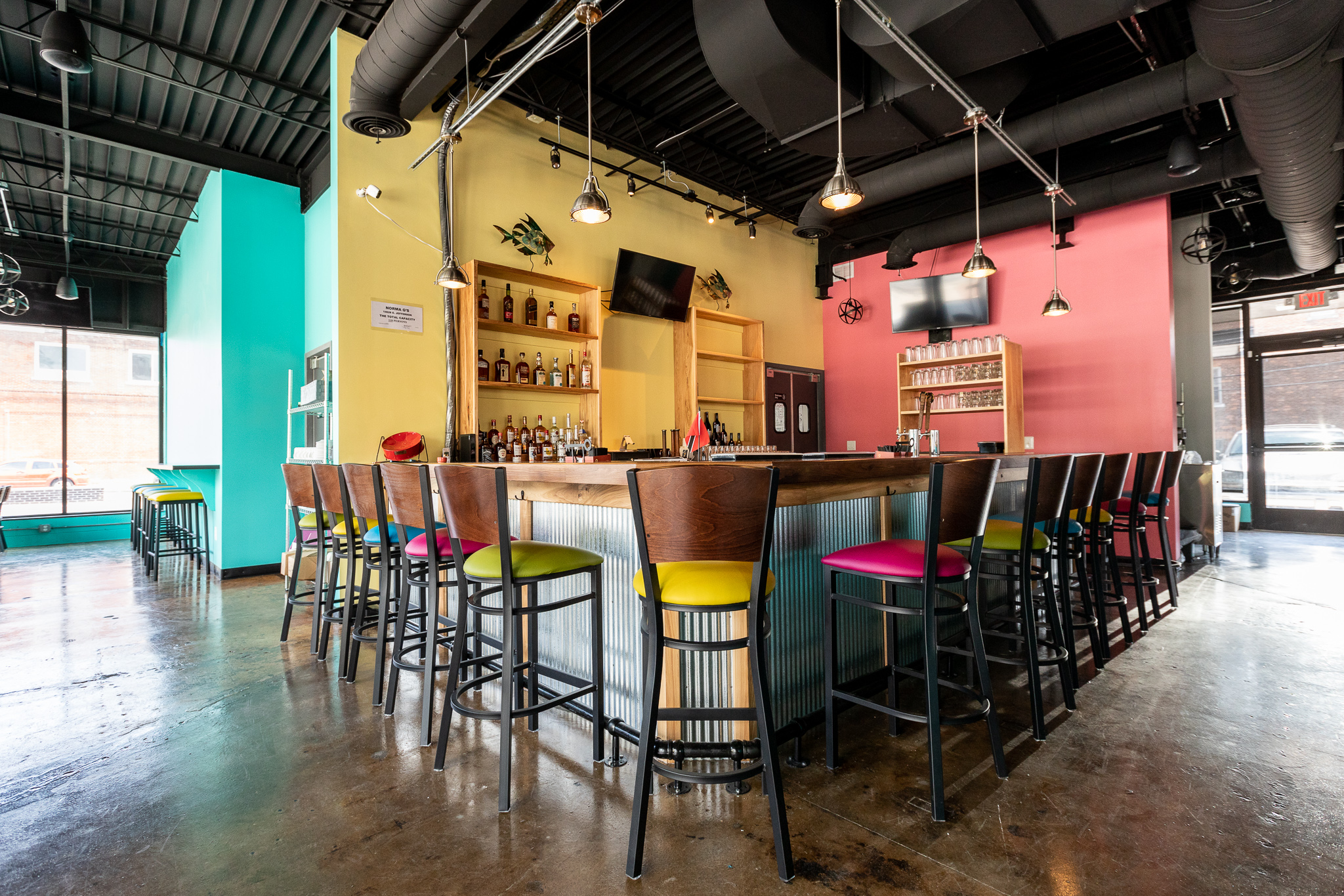 The bar at Norma G's features aqua, yellow, and coral colored walls with similarly colored bar stools.