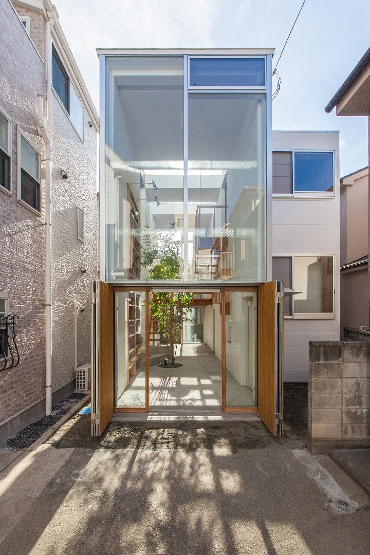 This home in Tokyo sits on a dead-end street and is composed of two narrow parallel volumes, with one hosting the basic amenities of a private home and the other acting as a public space that the sidewalk leads into and through. The home is clad in huge w