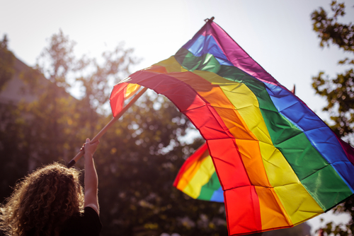 Photo of white woman from back waving a large, backlit Pride (rainbow) flag in city street.