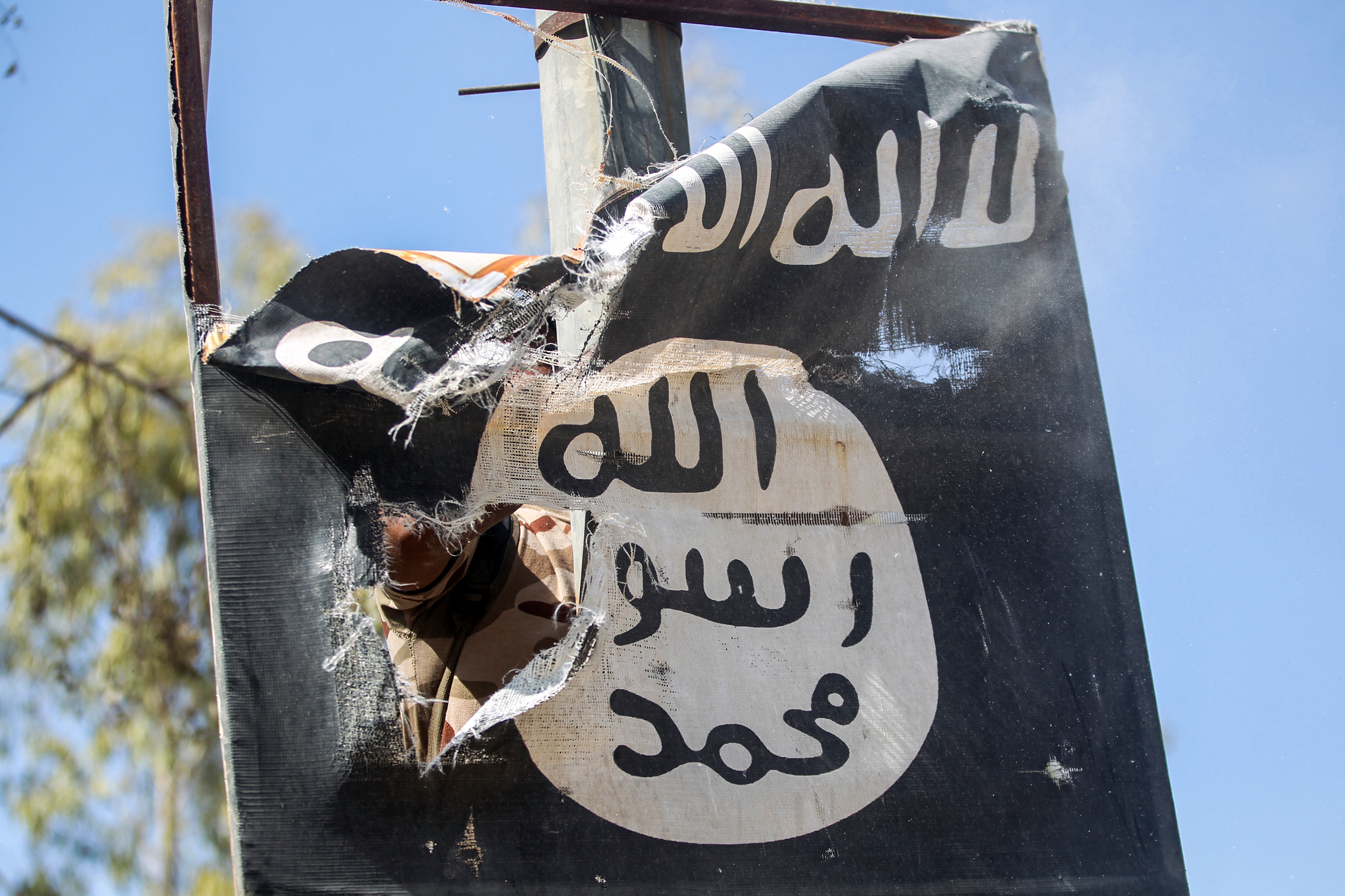 A member of Hashwd Al-Shaabi (Popular Mobilization units) removes a sign on a lamp post bearing the ISIS logo in the town of Tal Afar, Iraq, on August 26, 2017.