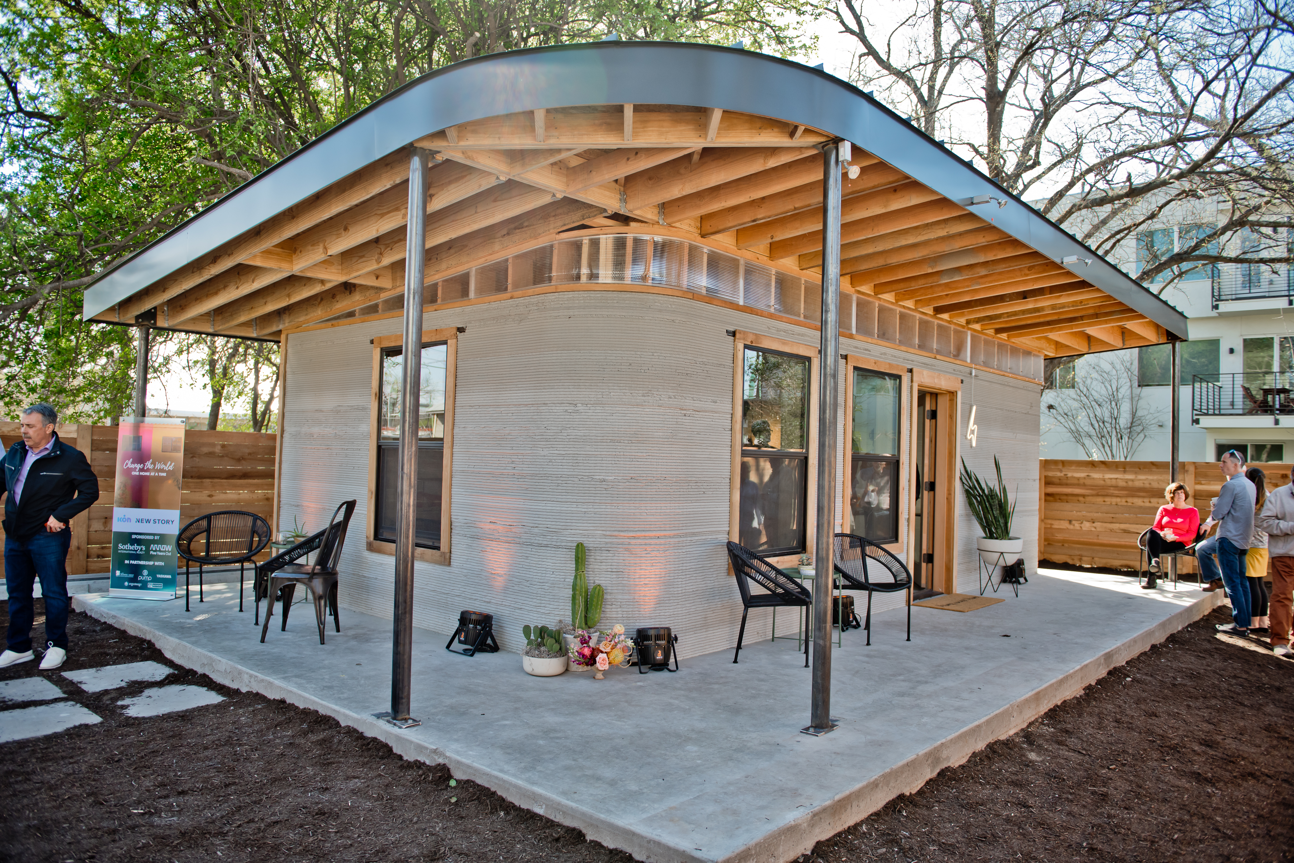 photo of a small cement house with curved walls covered wraparound porch