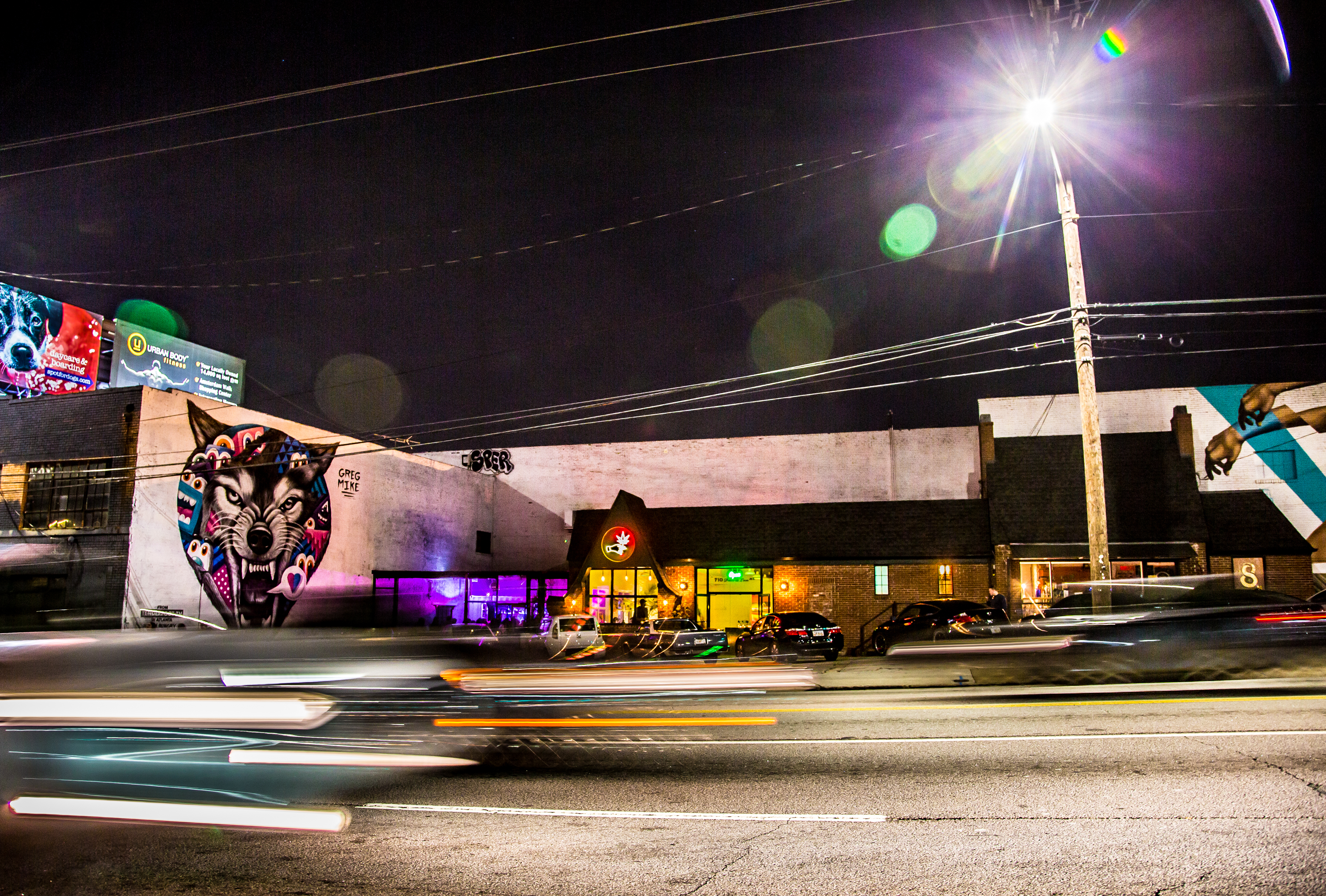 A nighttime shot of restaurant and bar 8ARM located on Ponce de Leon Avenue in Atlanta with cars rushing by