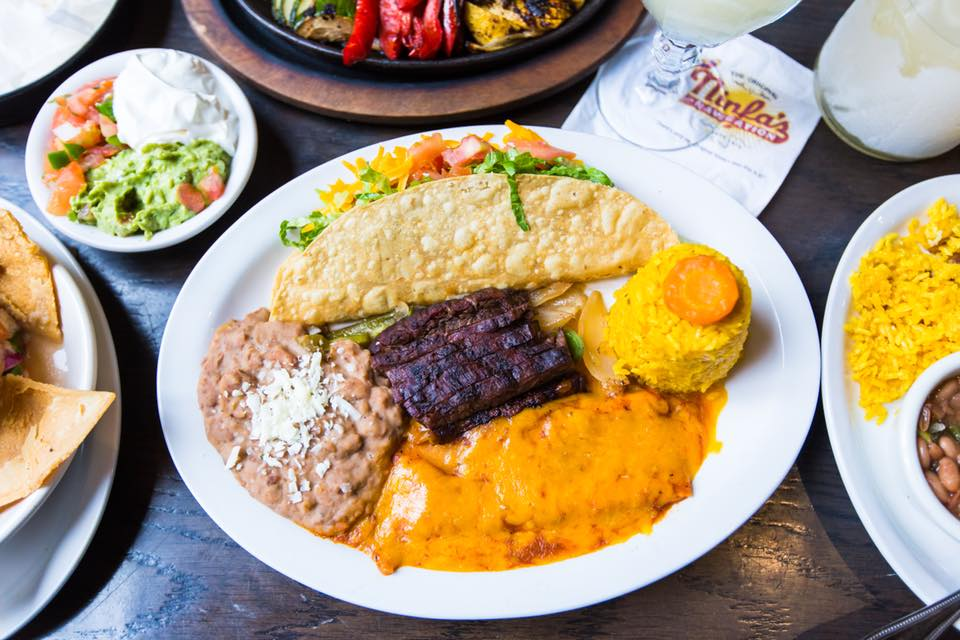 A taco, cheese-covered enchilada, beans, and rice, on a white plate. Guacamole, sour cream, and other condiments sit in a white bowl to the left.