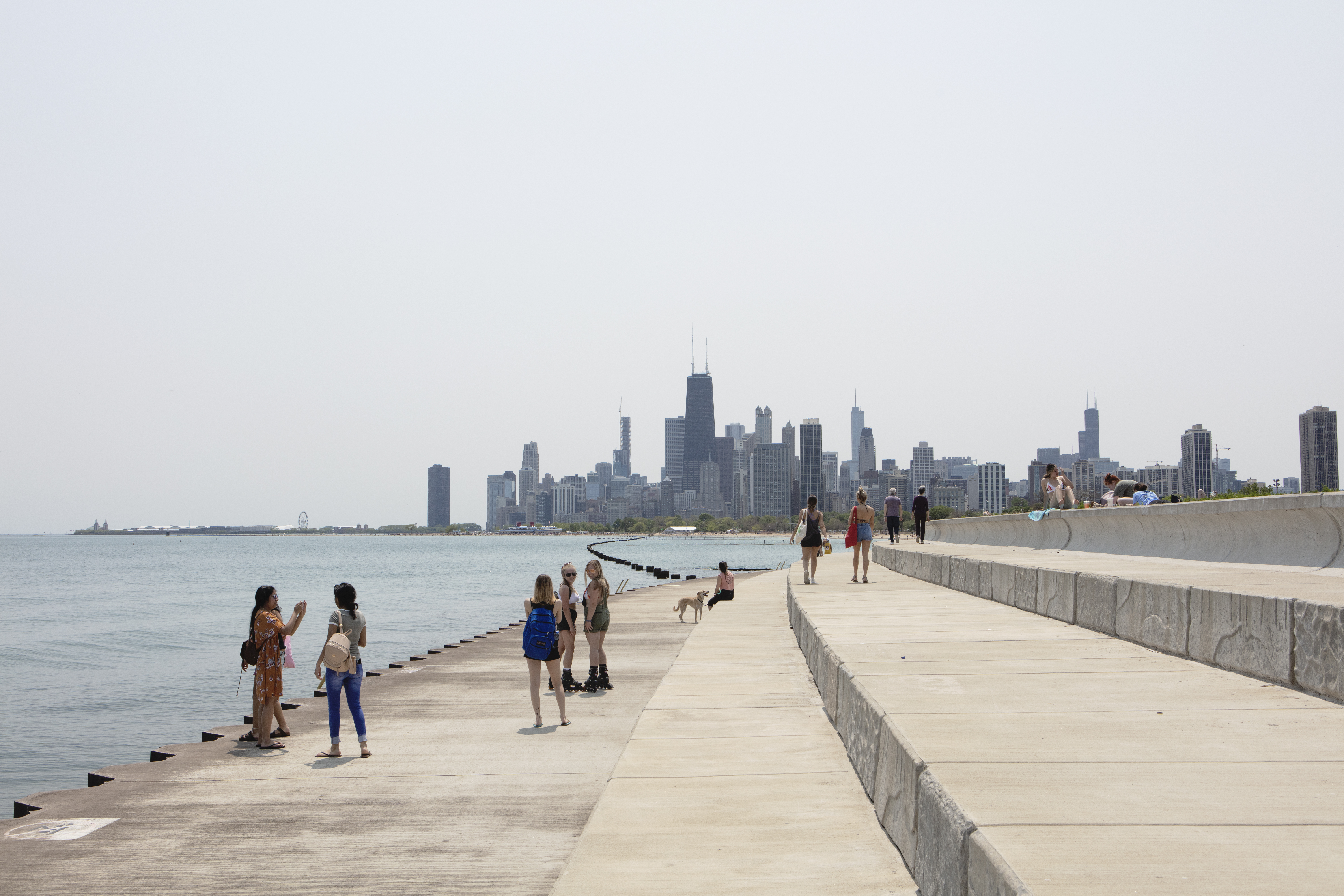 A tiered concrete breakwater curves around the edge of the a lake with small groups of people strolling in the sun with tall towers and buildings in the distance.
