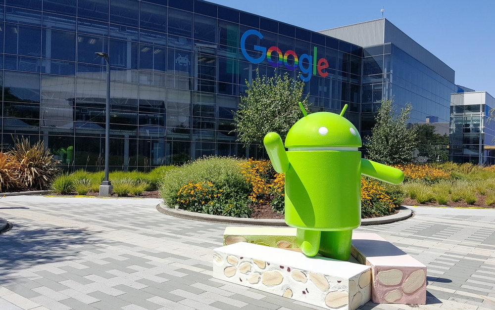 The Google headquarters. There is a glass building with the word Google on it. In front of the building is a statue of a green android.