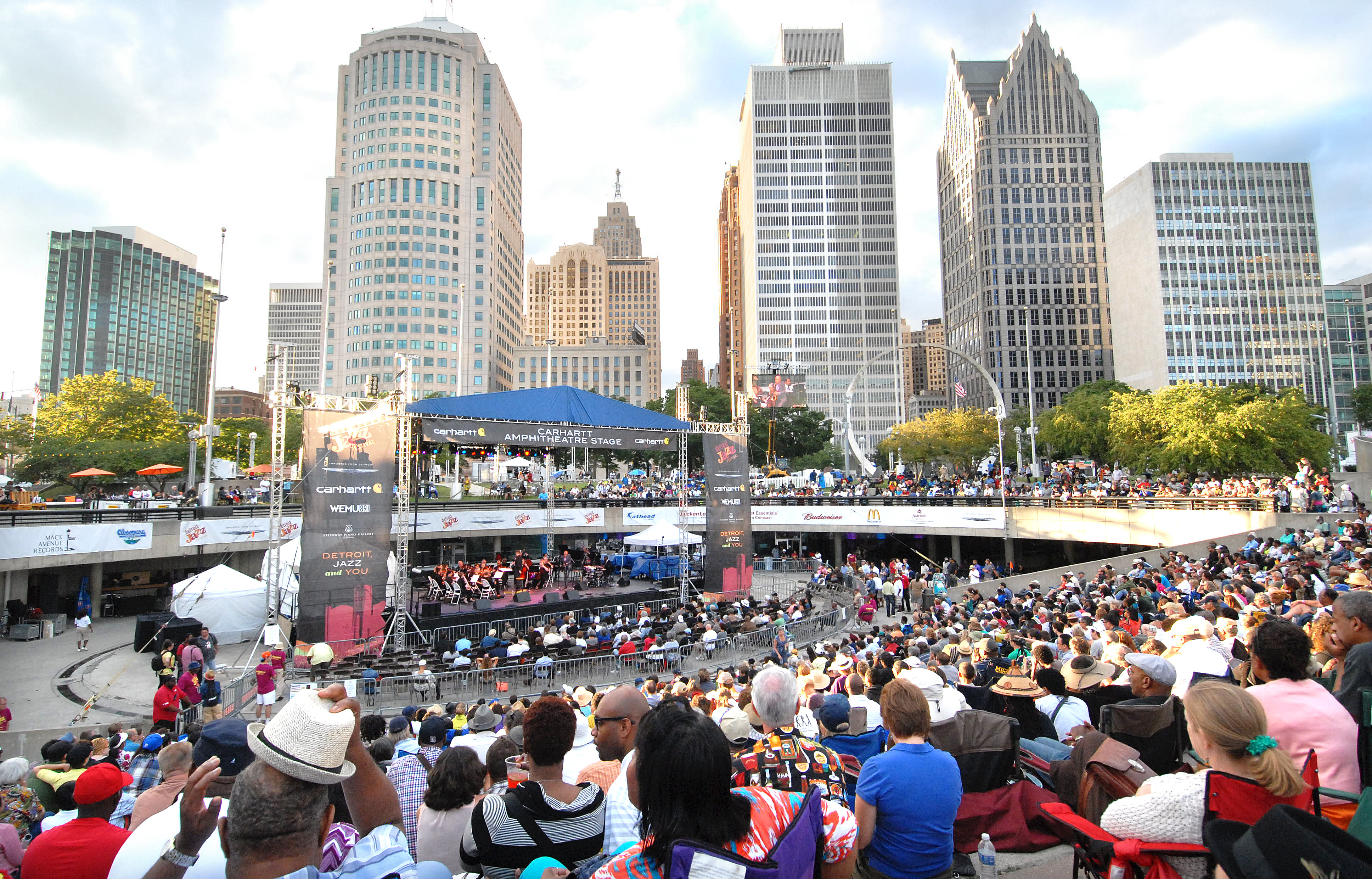 A huge crowd sits around a depressed amphitheater with a row of tall skyscrapers in the background.