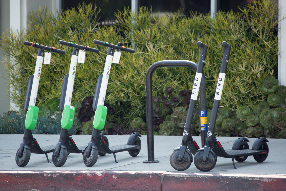 Electric scooters lined up on an LA sidewalk.