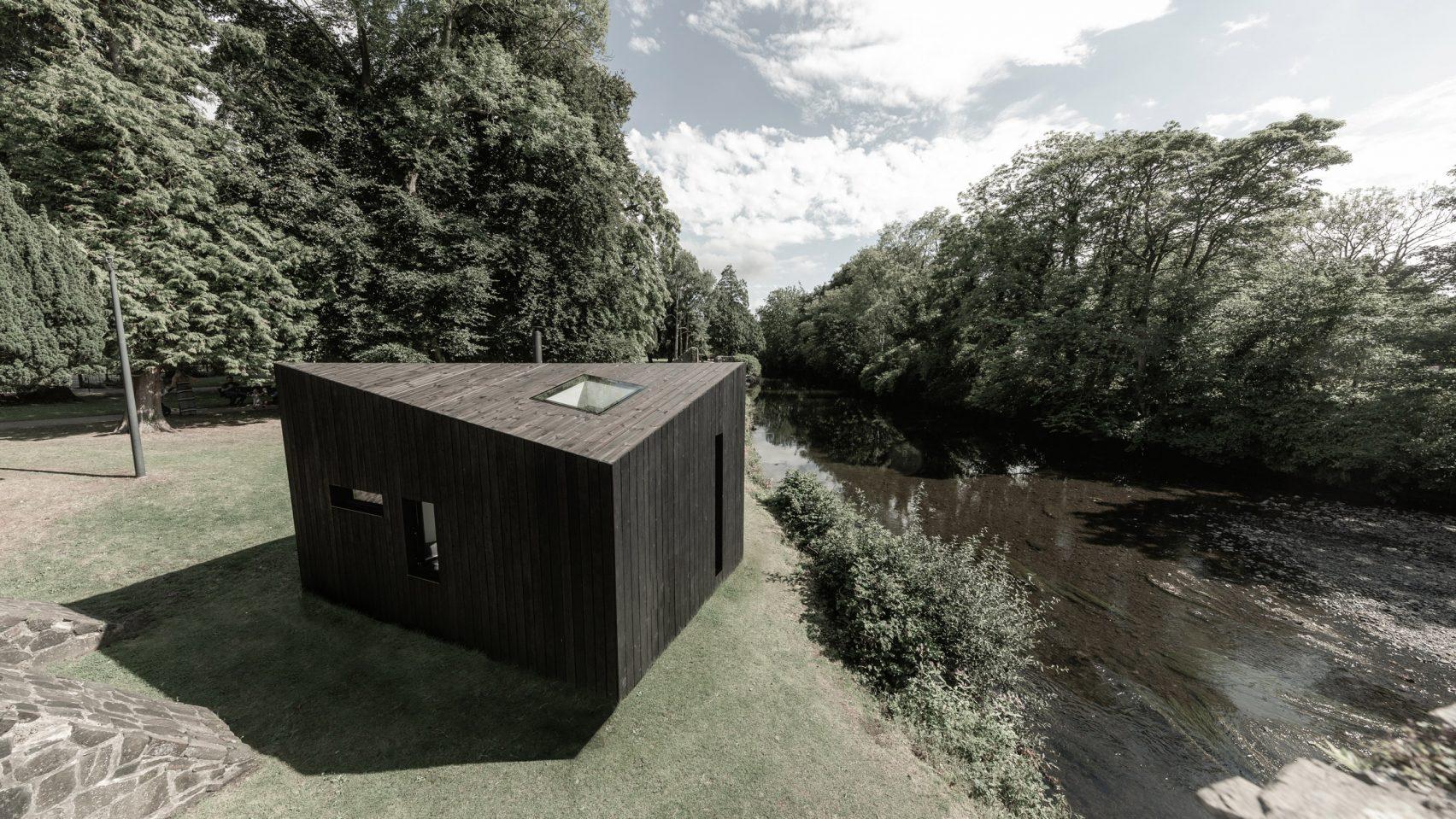 Aerial shot of triangular black wood cabin