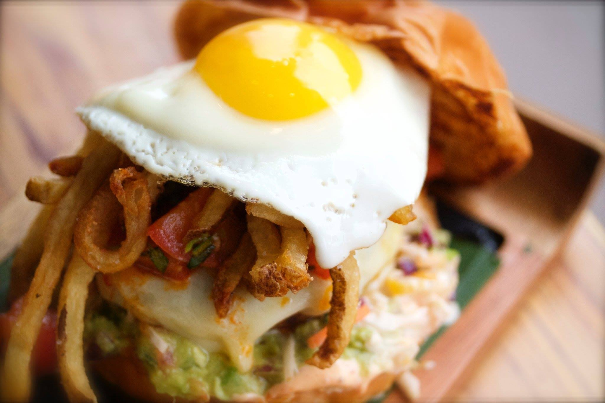 A burger on a brioche bun with shoestring fries and a fried egg.