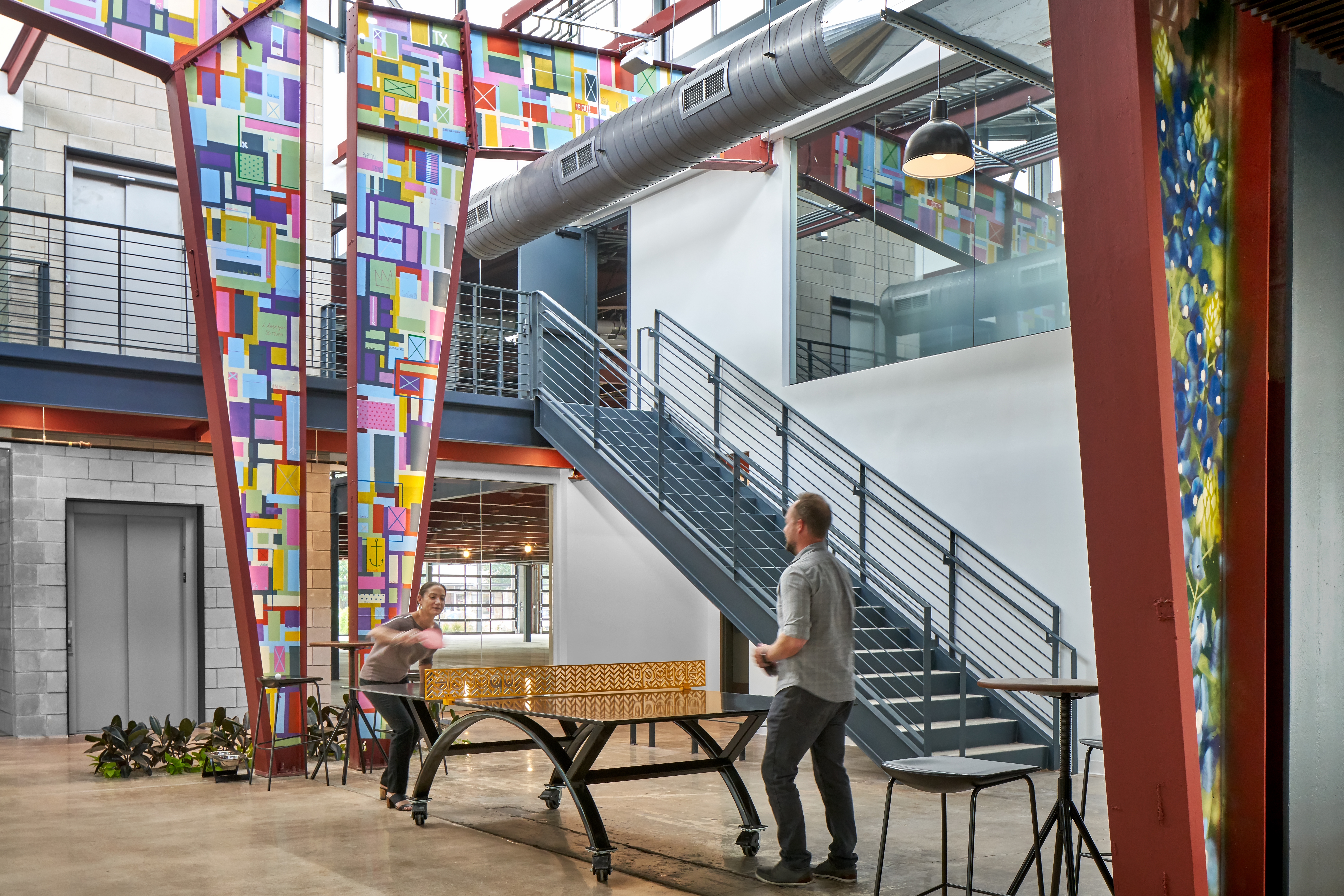 Large, open, two-story space with metal support columns painted colorfully, stairs, tables, chairs