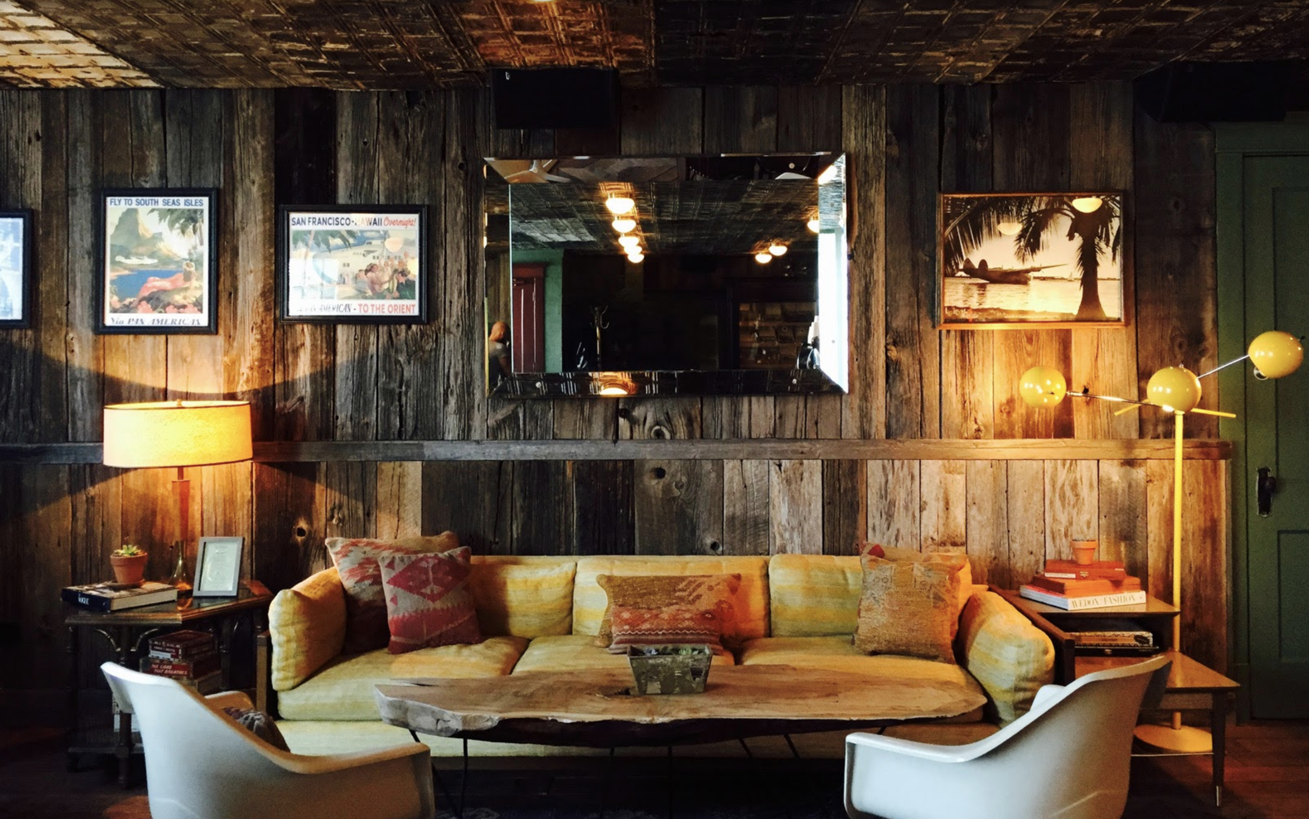 The interior of a restaurant. There is a couch with multiple assorted pillows. There are chairs. The walls are wood paneled.