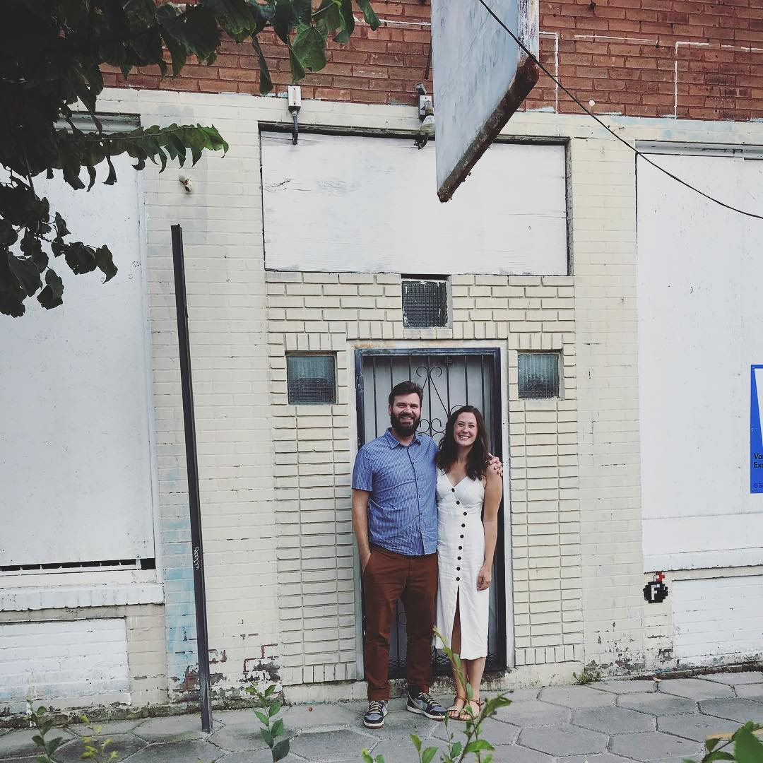 Emma and Sean Schacke standing in front of the white building before the renovation
