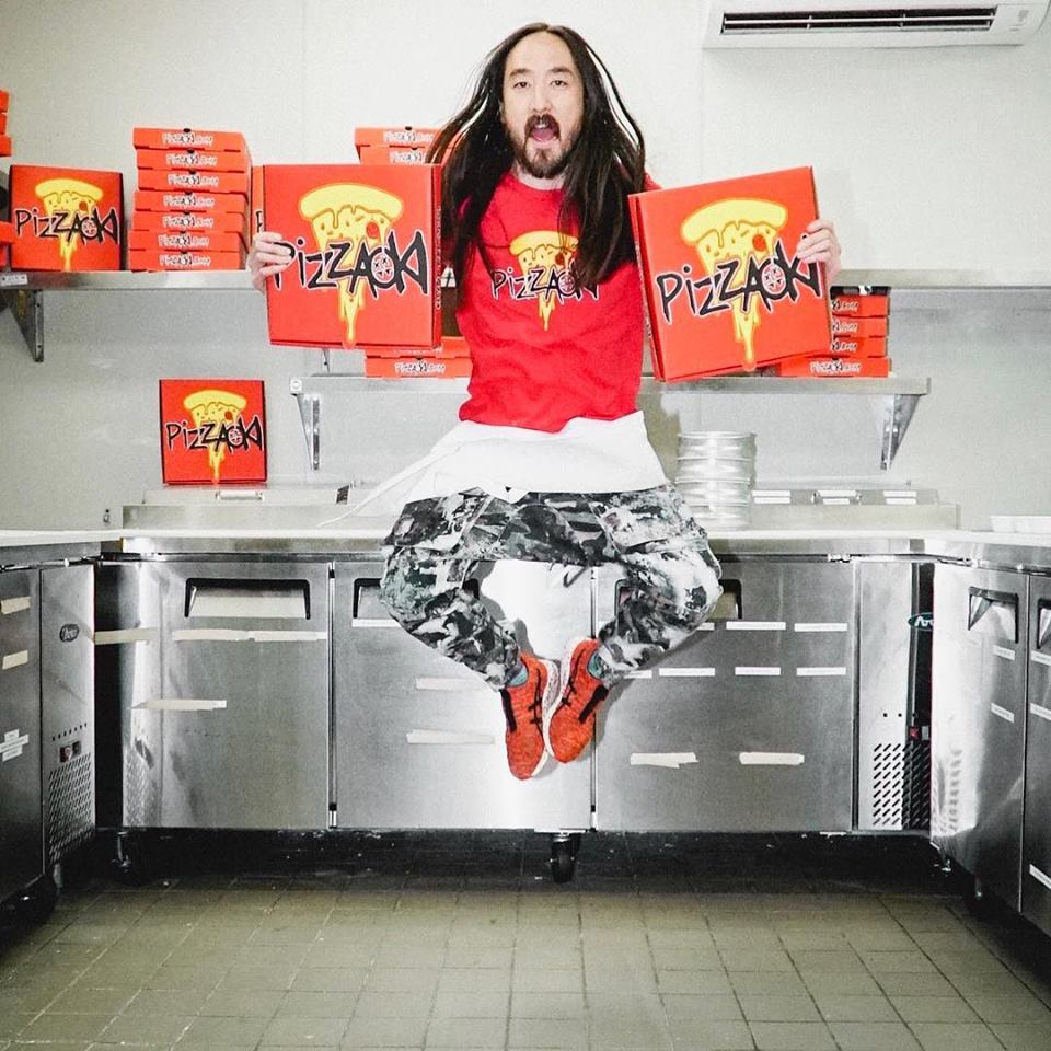 Steve Aoki levitating in a kitchen holding two pizzaoki boxes.