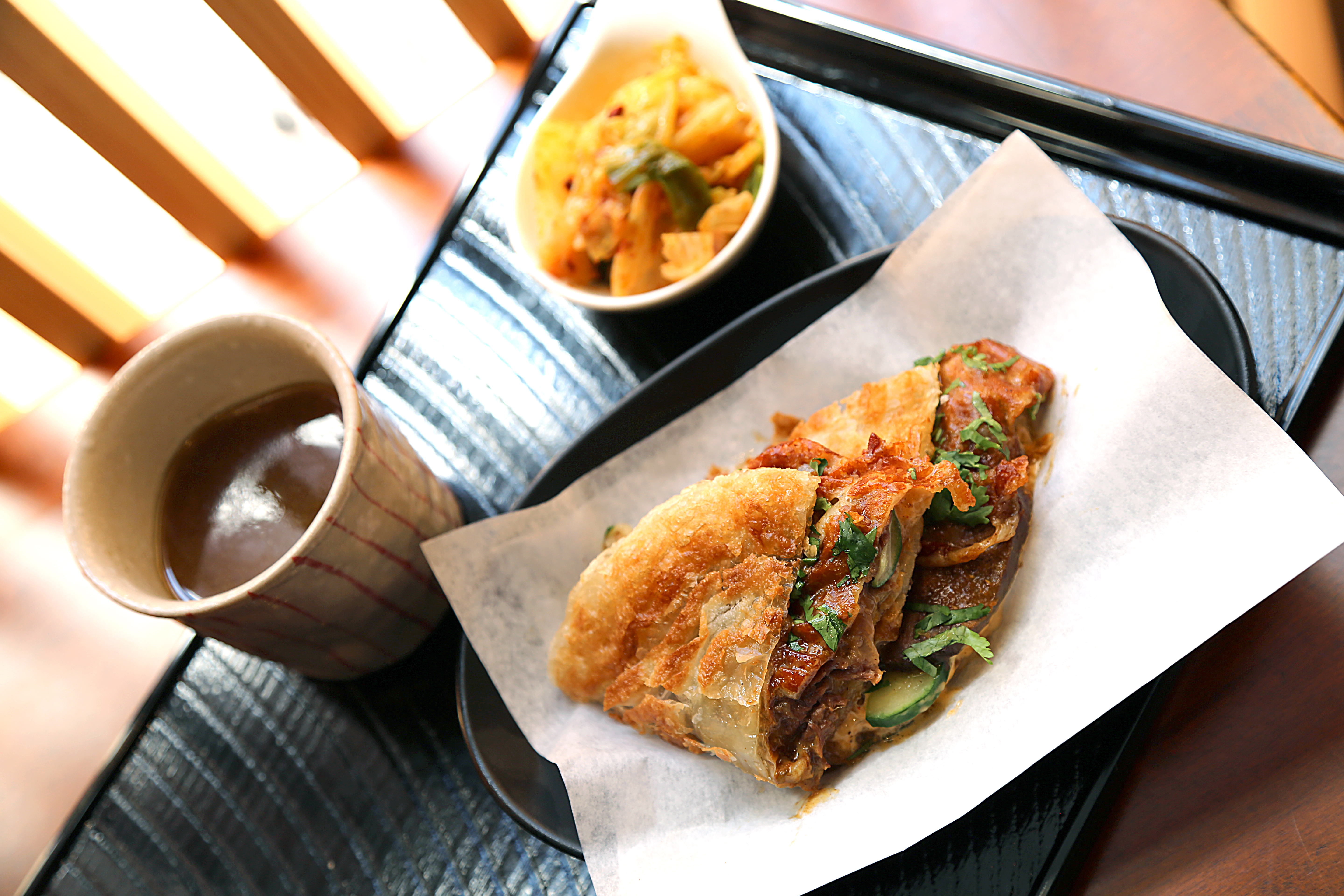 A crispy sandwich filled with meat rests on parchment paper in a plastic dining tray. Beside it, there is a dark beverage and a side of pickled vegetables.