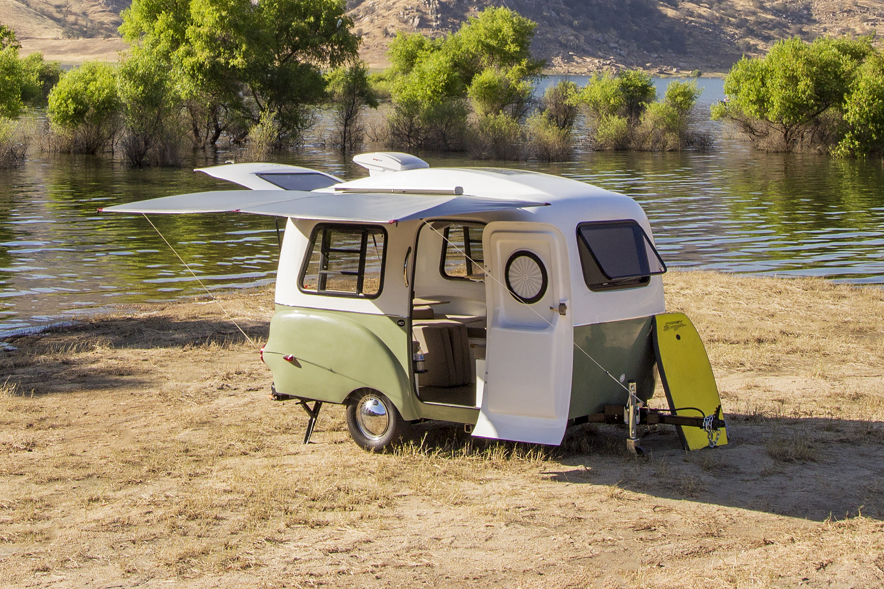 A camper van sitting in a clearing adjacent to a body of water. The van is white and green. All of the van's doors are open.