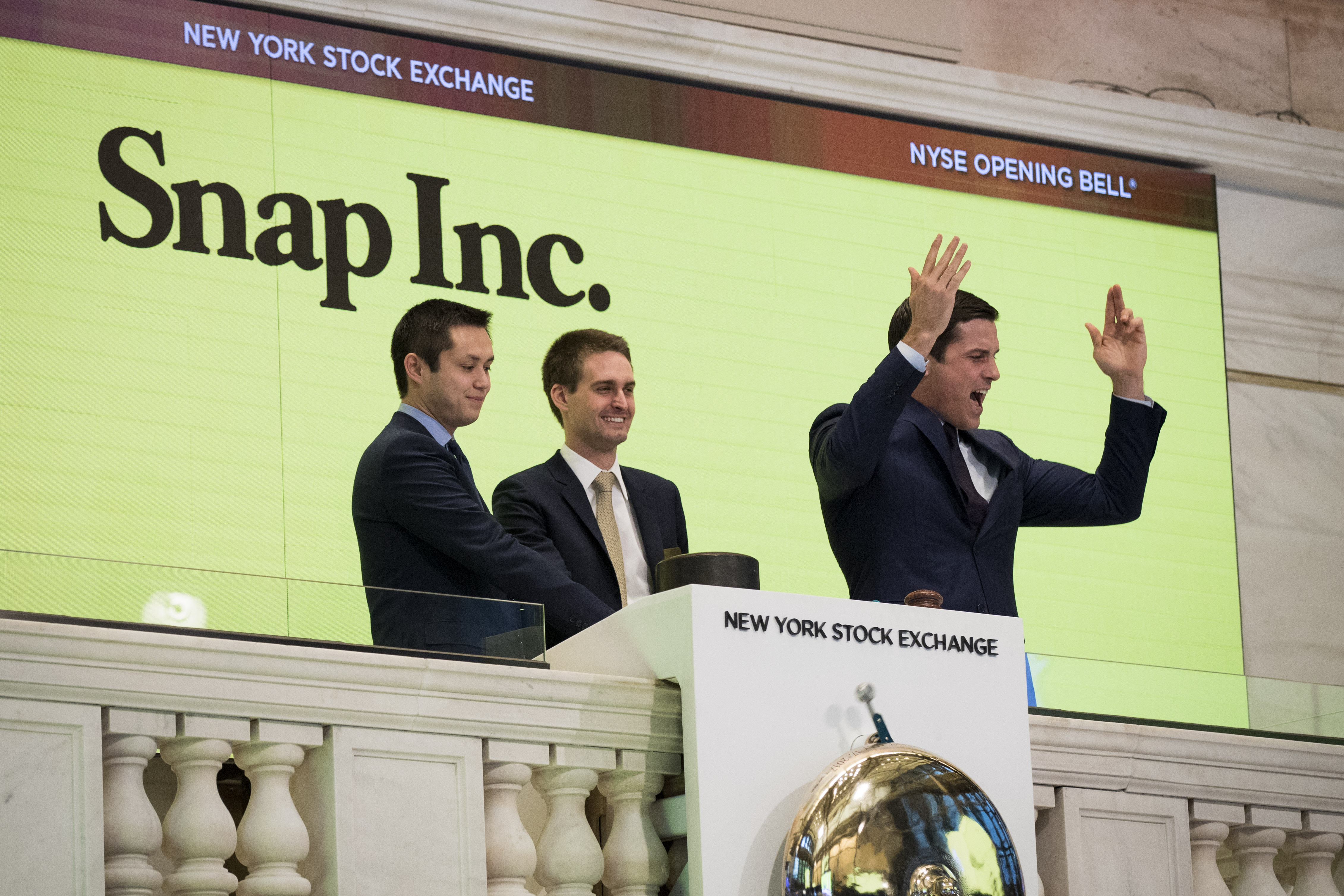 """Snapchat co-founders Bobby Murphy and Evan Spiegel ring the opening bellon the NYSE in front of a sign reading """"Snap Inc."""""""