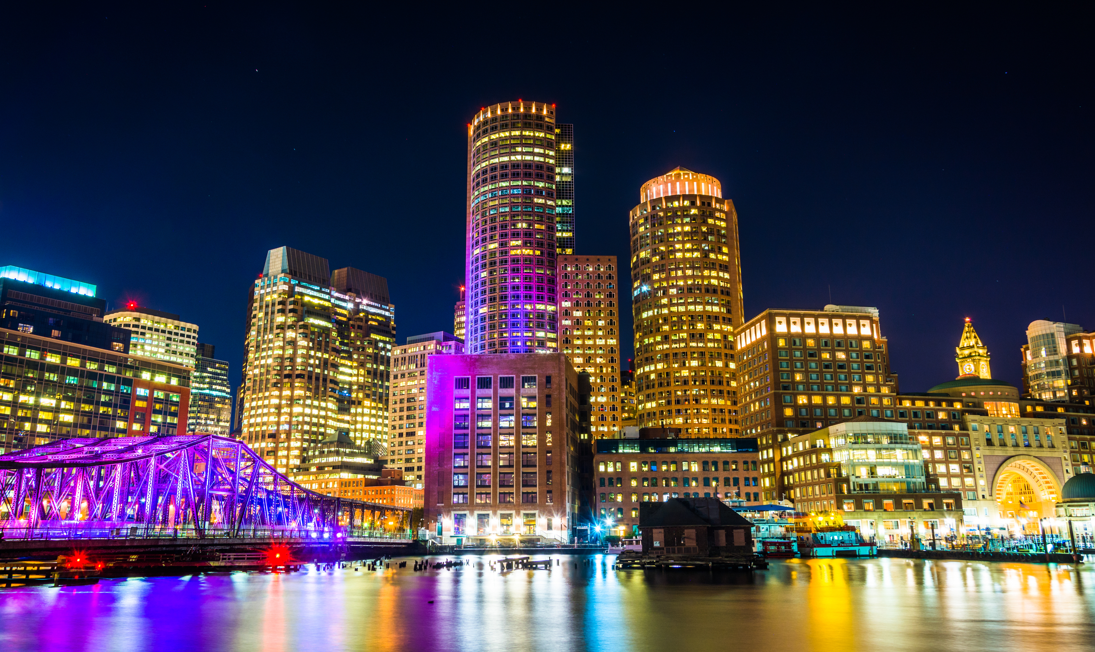 A nighttime view of the Boston skyline, focusing on a slice of the Financial District