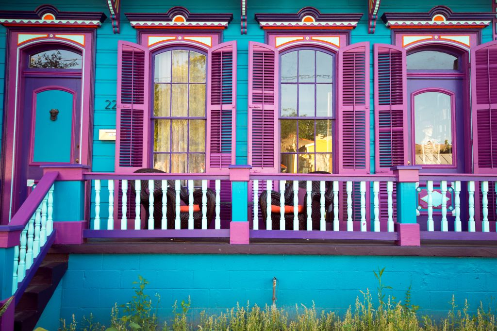 A bright blue Victorian home with purple shutters