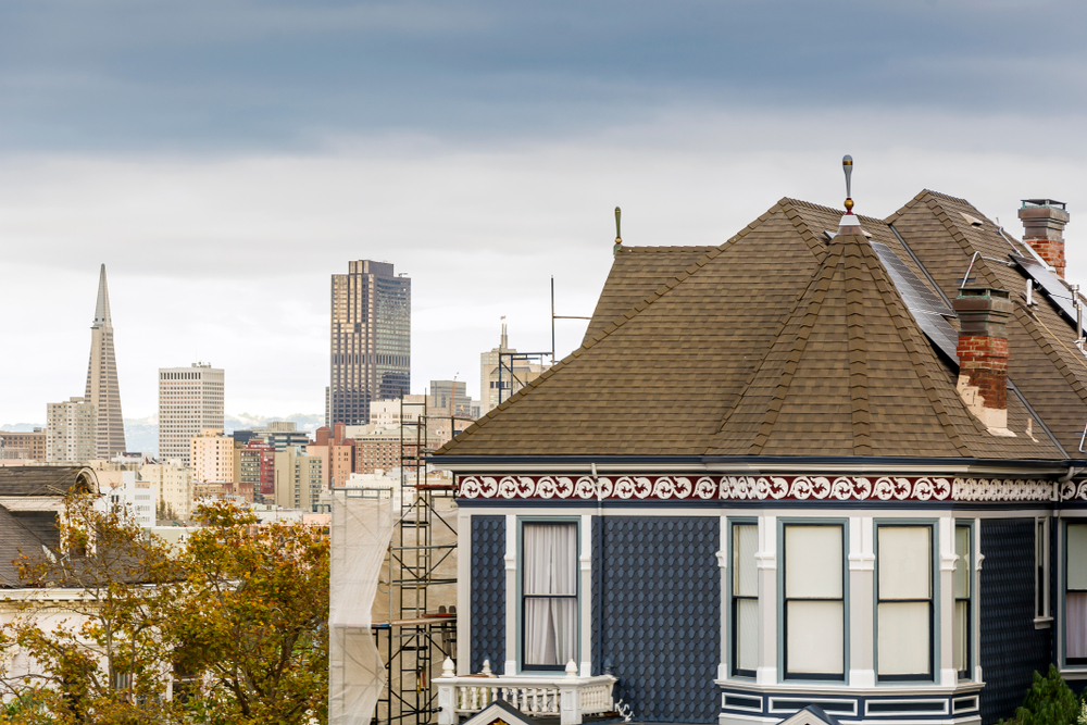 Closeup of a Victorian house in SF with the skyline visible over the roof.