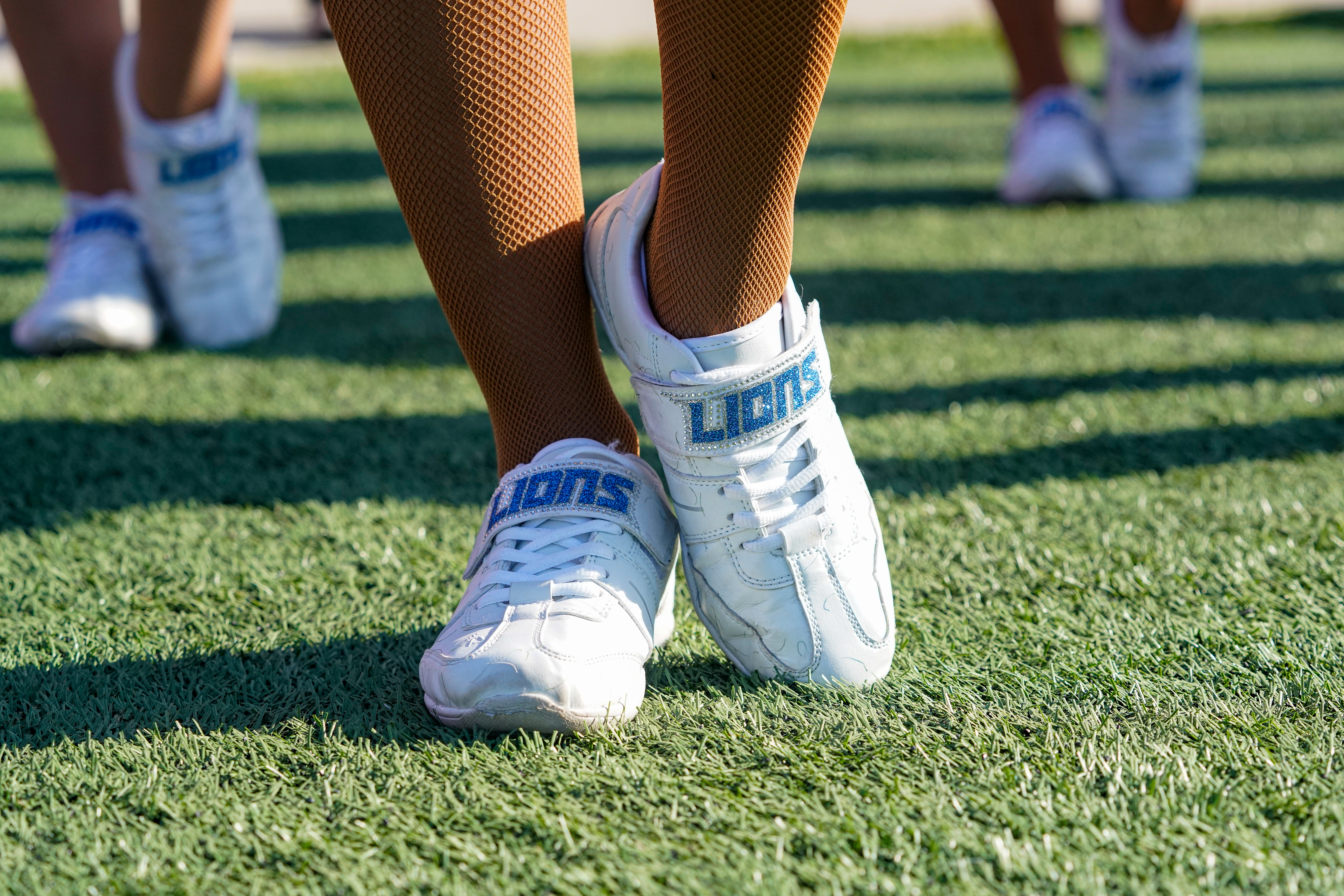 A cheerleader's shoes are imprinted with the word Lions