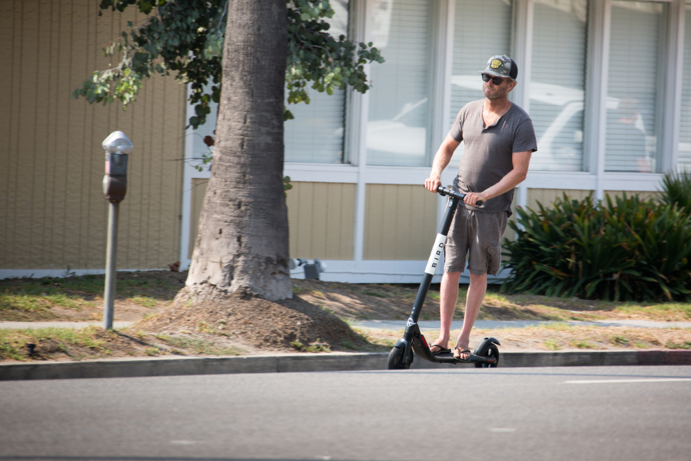 A man (without a helmet) riding an e-scooter in LA.