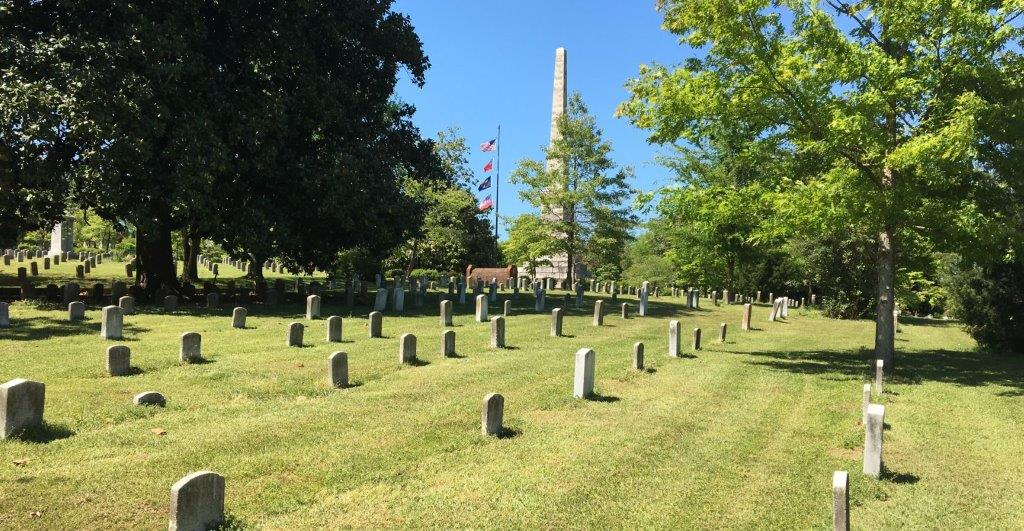 A field of headstones, with a memorial obelisk beyond.