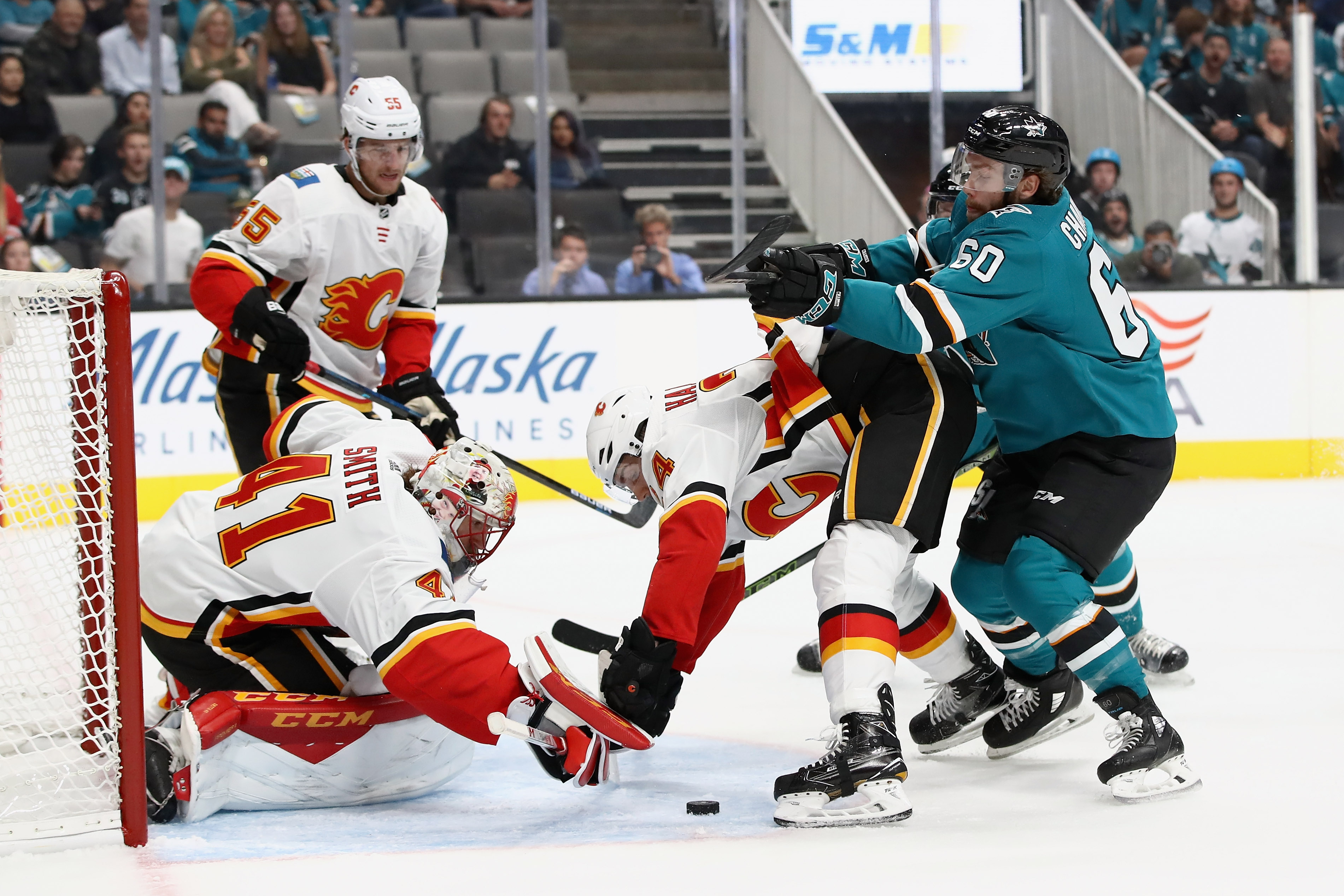 SAN JOSE, CA - SEPTEMBER 27: Mike Smith #41 and Travis Hamonic #24 of the Calgary Flames stop Rourke Chartier #60 of the San Jose Sharks from scoring during their preseason game at SAP Center on September 27, 2018 in San Jose, California.