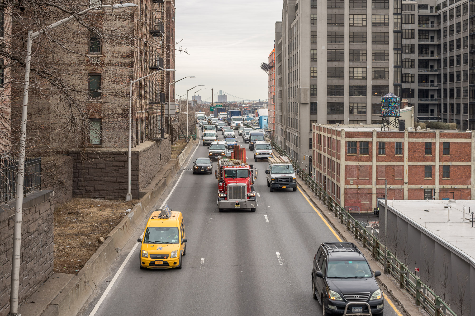 A yellow cab, a red truck, and several other cars driving on the Brooklyn Heights section of the Brooklyn Queens Expressway.