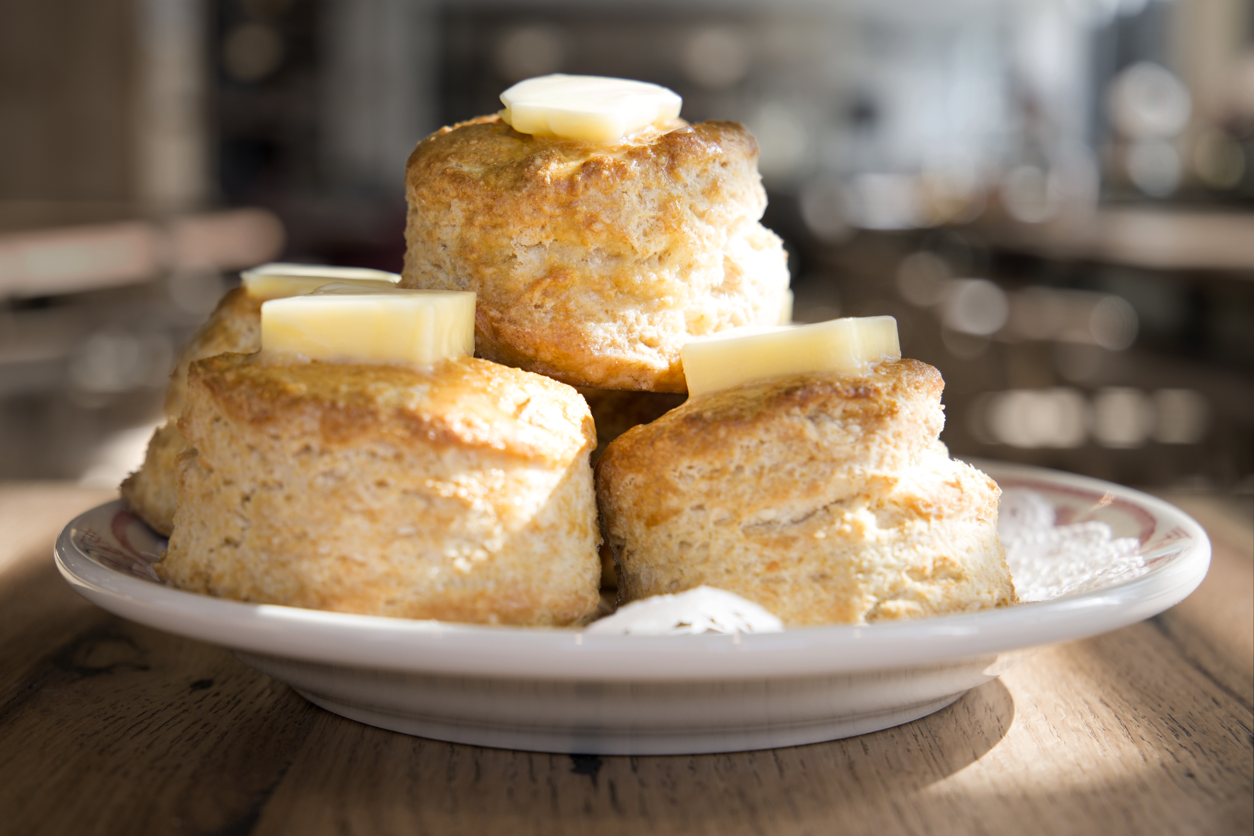 Biscuits stacked in a triangle are topped with thick squares of butter at Southern Proper in Boston's South End