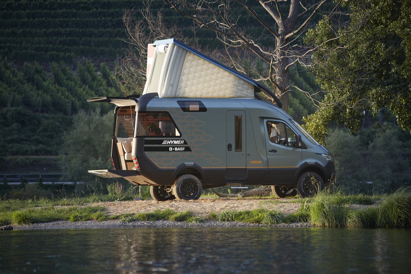 A modern camper van sits by a lake. The camper van boasts an open back door with small deck and a white pop-up sleeping area on the roof.