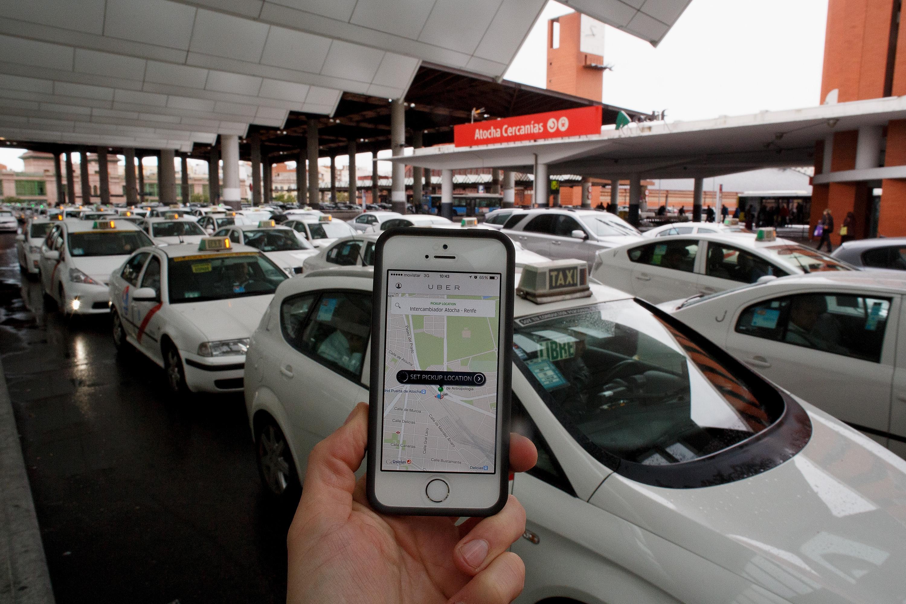 a smartphone screen with the Uber app in front of a train station