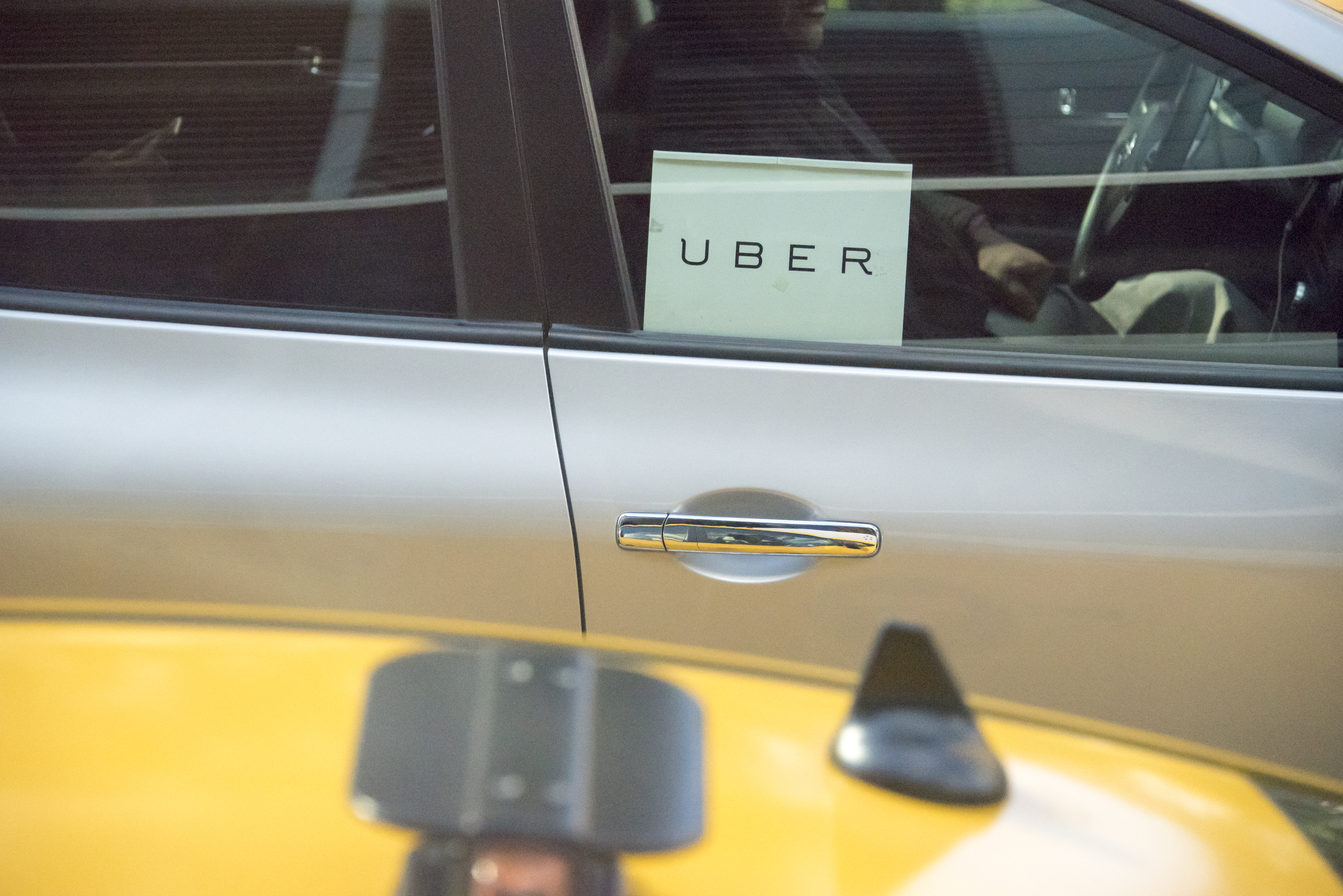 A car with an Uber sign in the window beside a yellow taxi