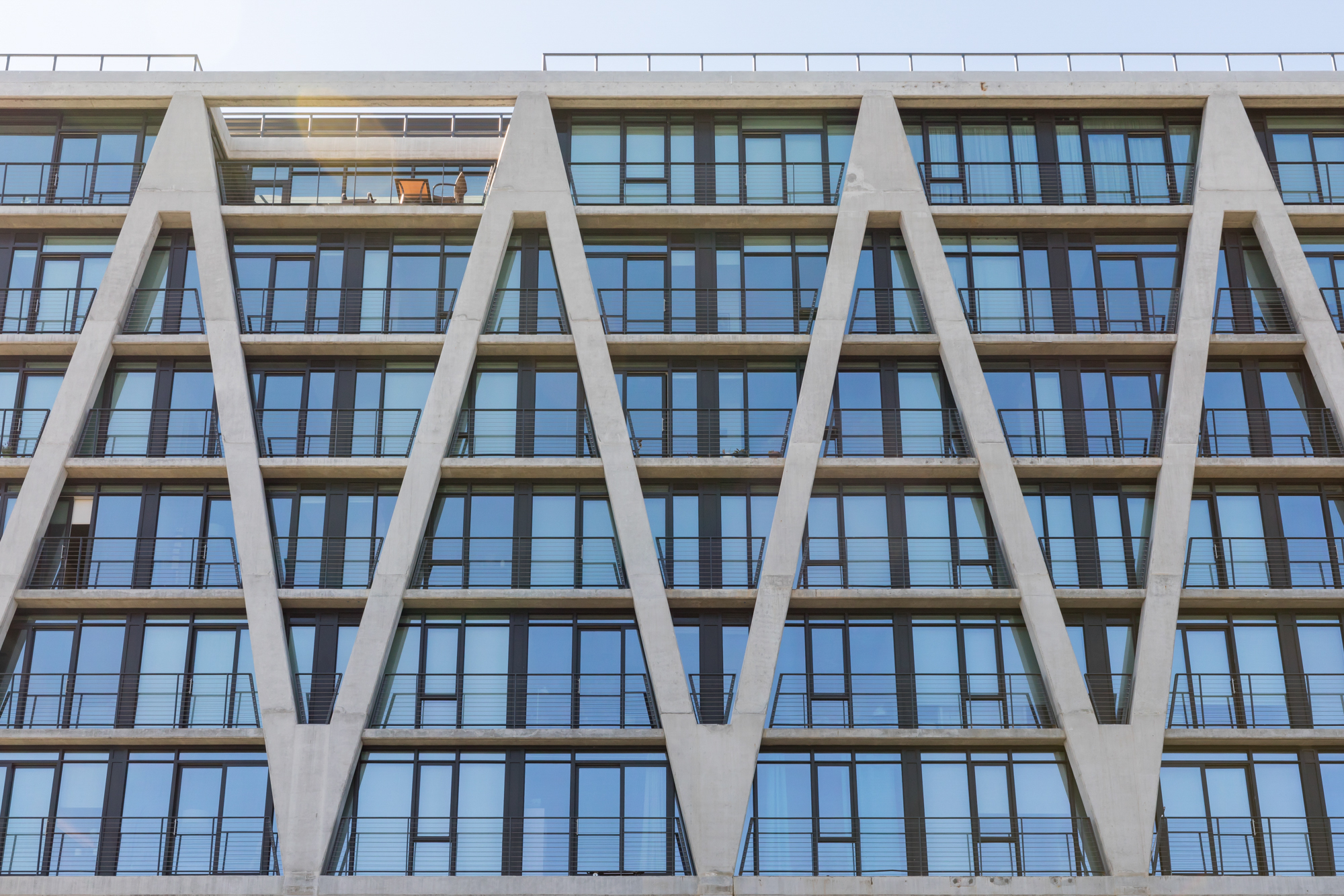 Exterior of high-rise with a grey, concrete, zig-zagging skeletal facade.