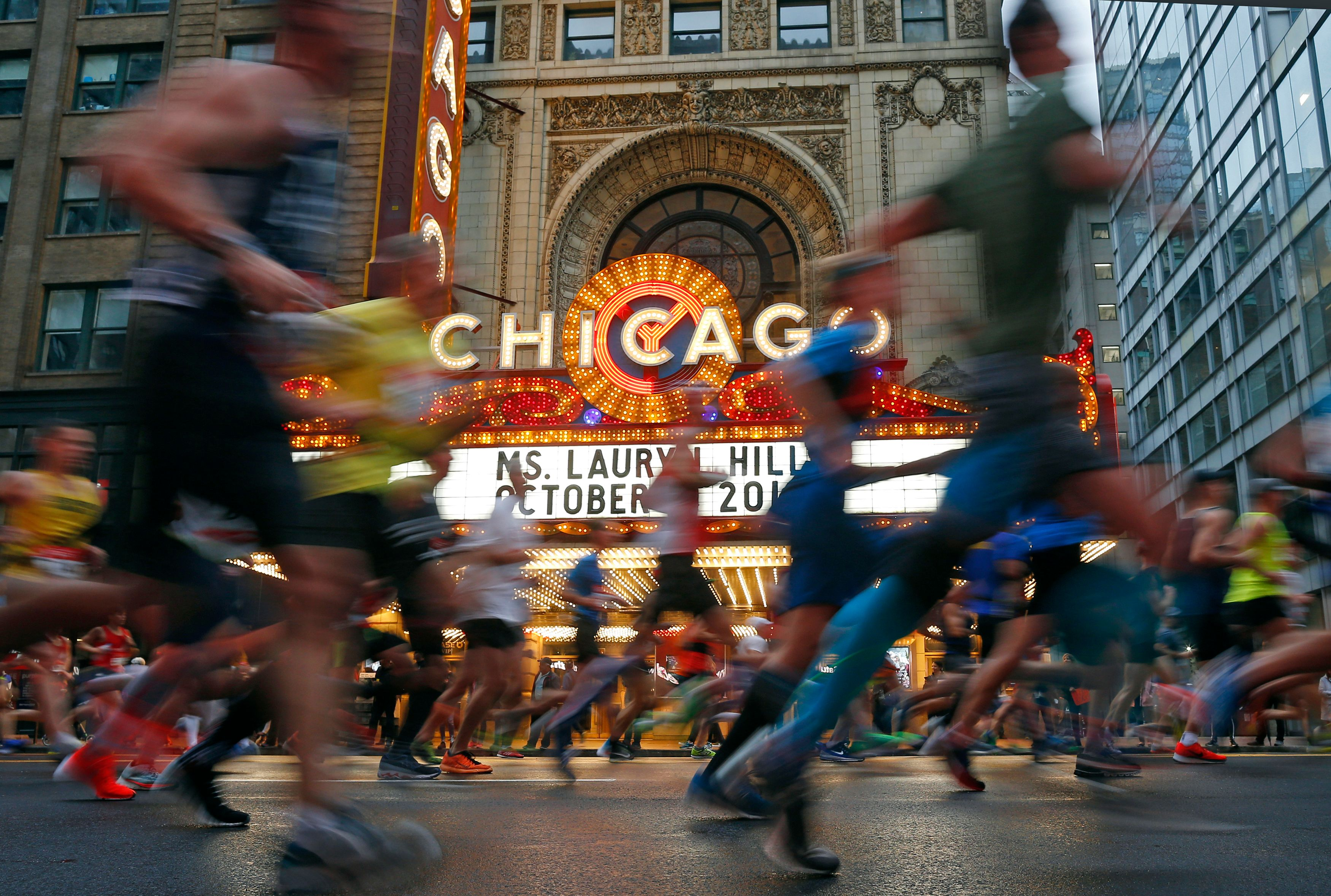 Groups of runners jogging in the Chicago Marathon pass the marquee of the Chicago Theatre on State Street.