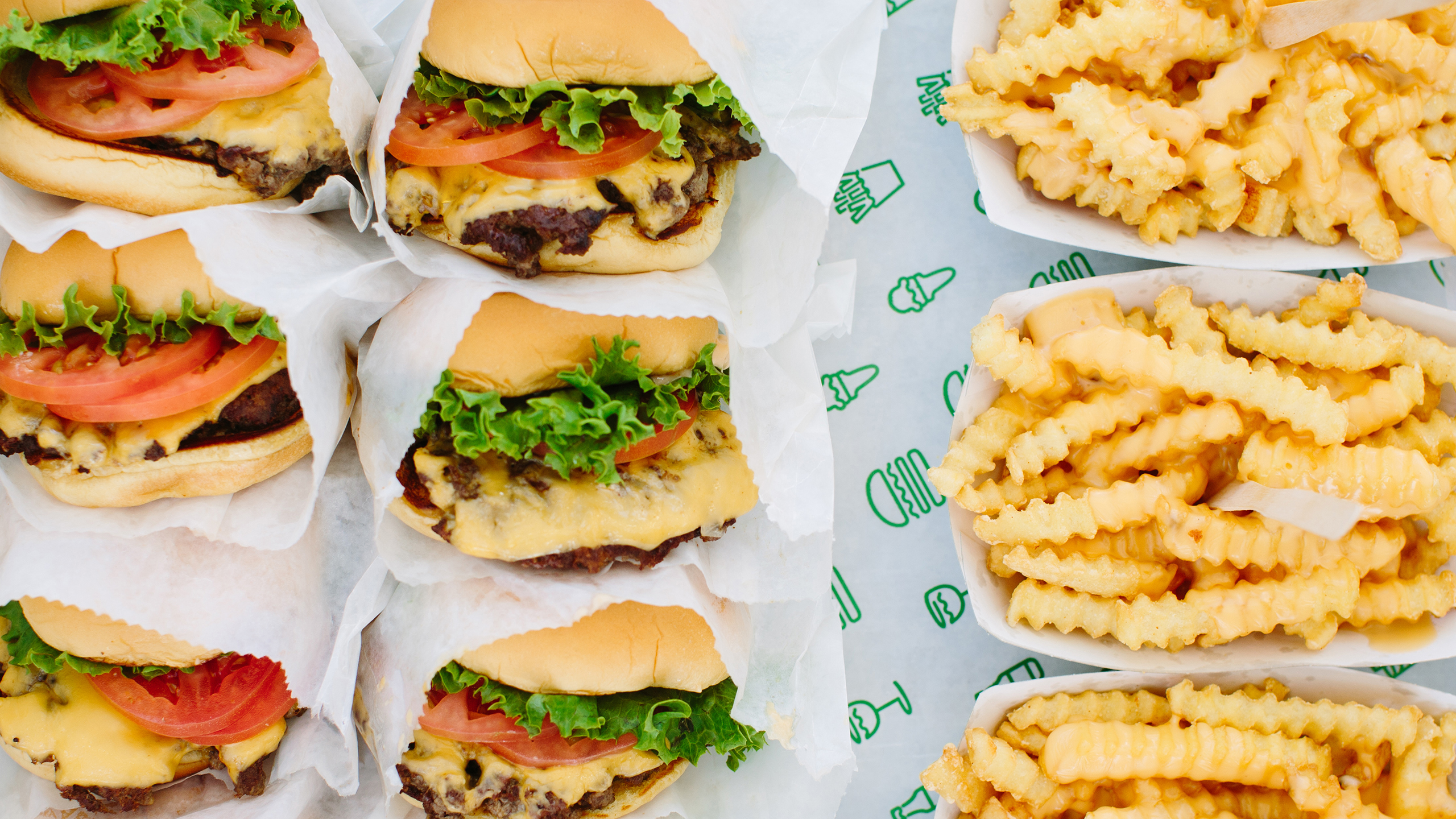 A full tray of burgers and crinkle-cut fries from Shake Shack, shown above.