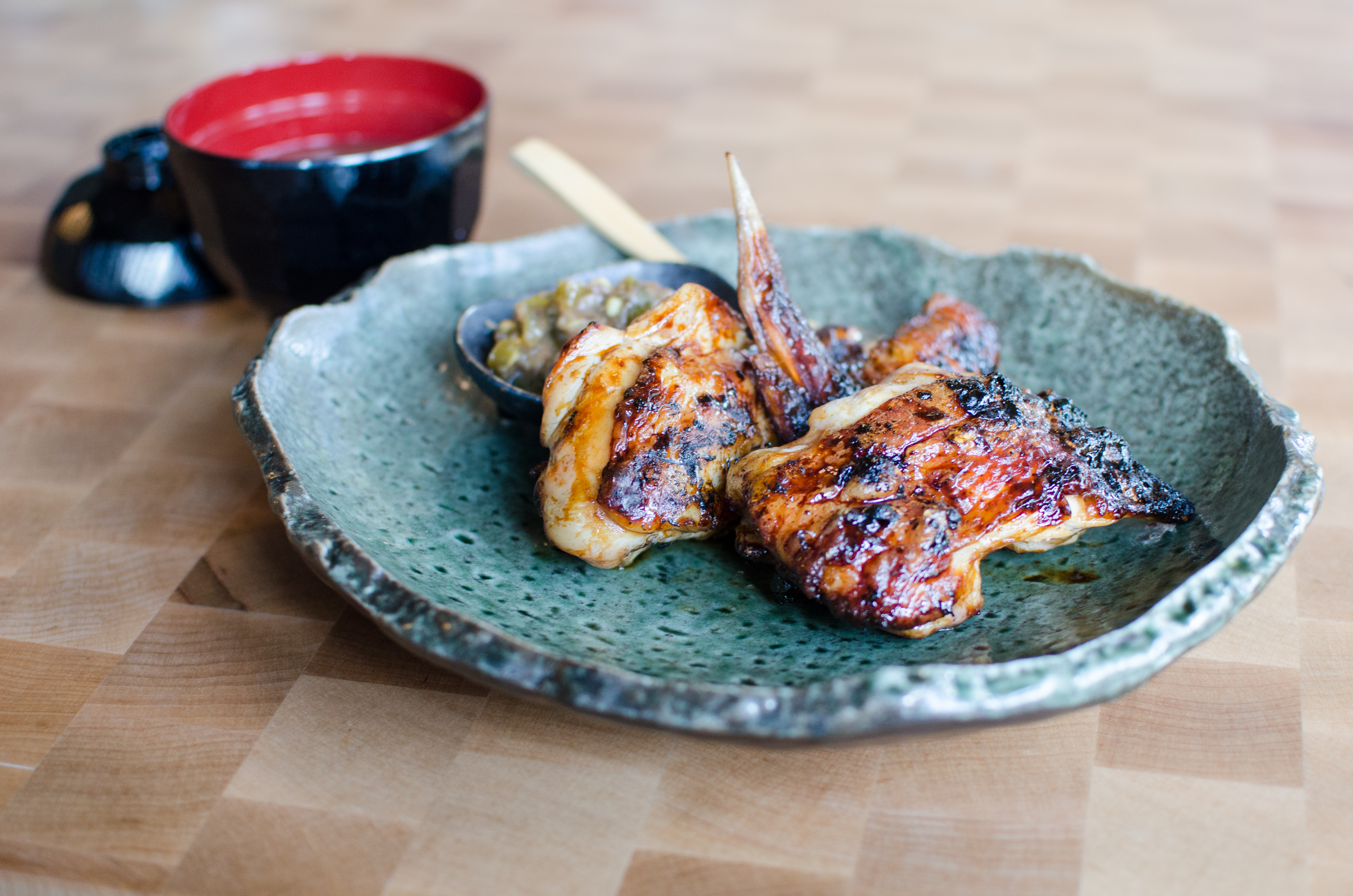 Grilled chicken sits on a light blue plate with rough edges, alongside a small black and red bowl full of broth
