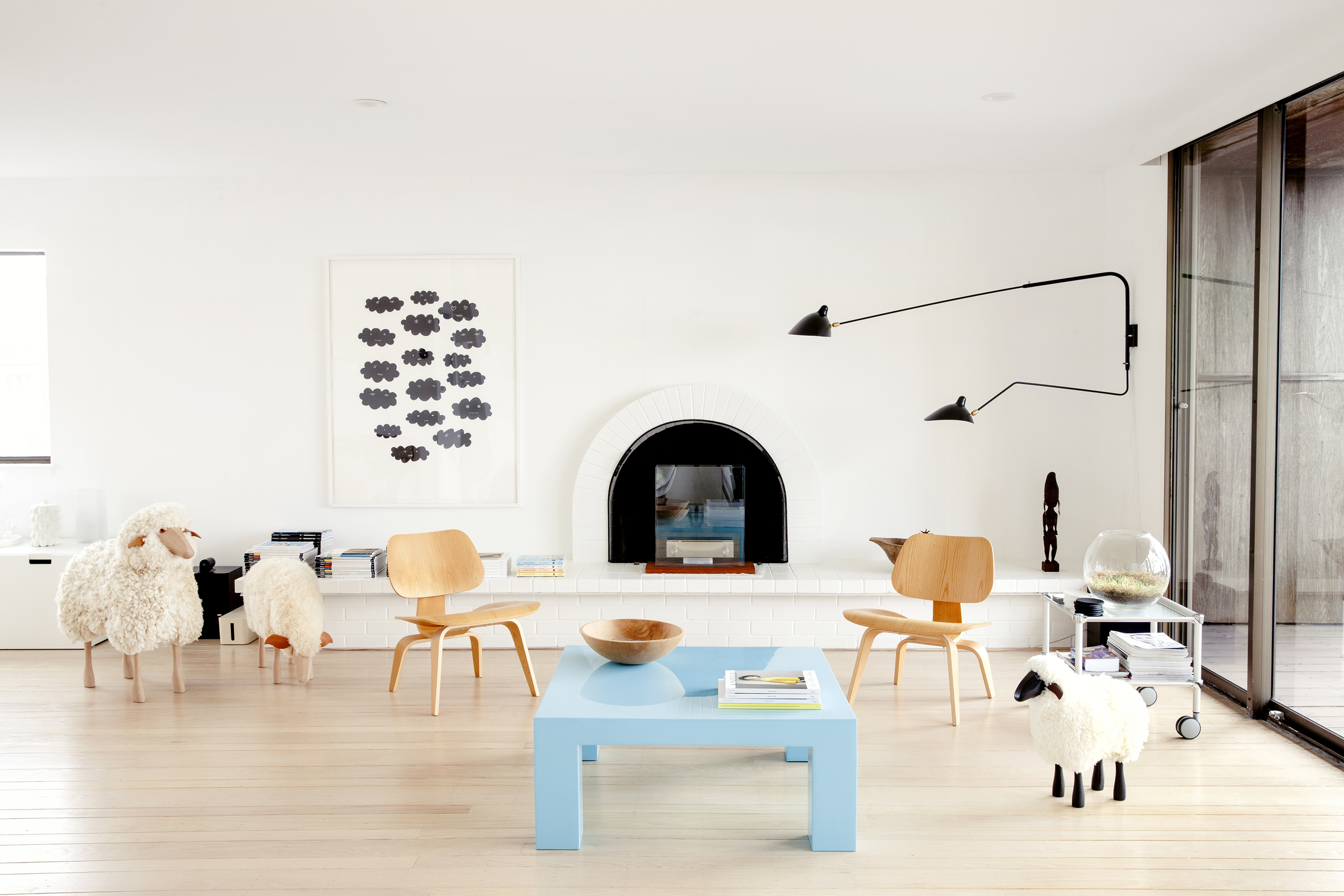 A living area with a blue table, chairs, lamps, and multiple sheep dolls. The floor is hardwood. There is a work of art on the wall.
