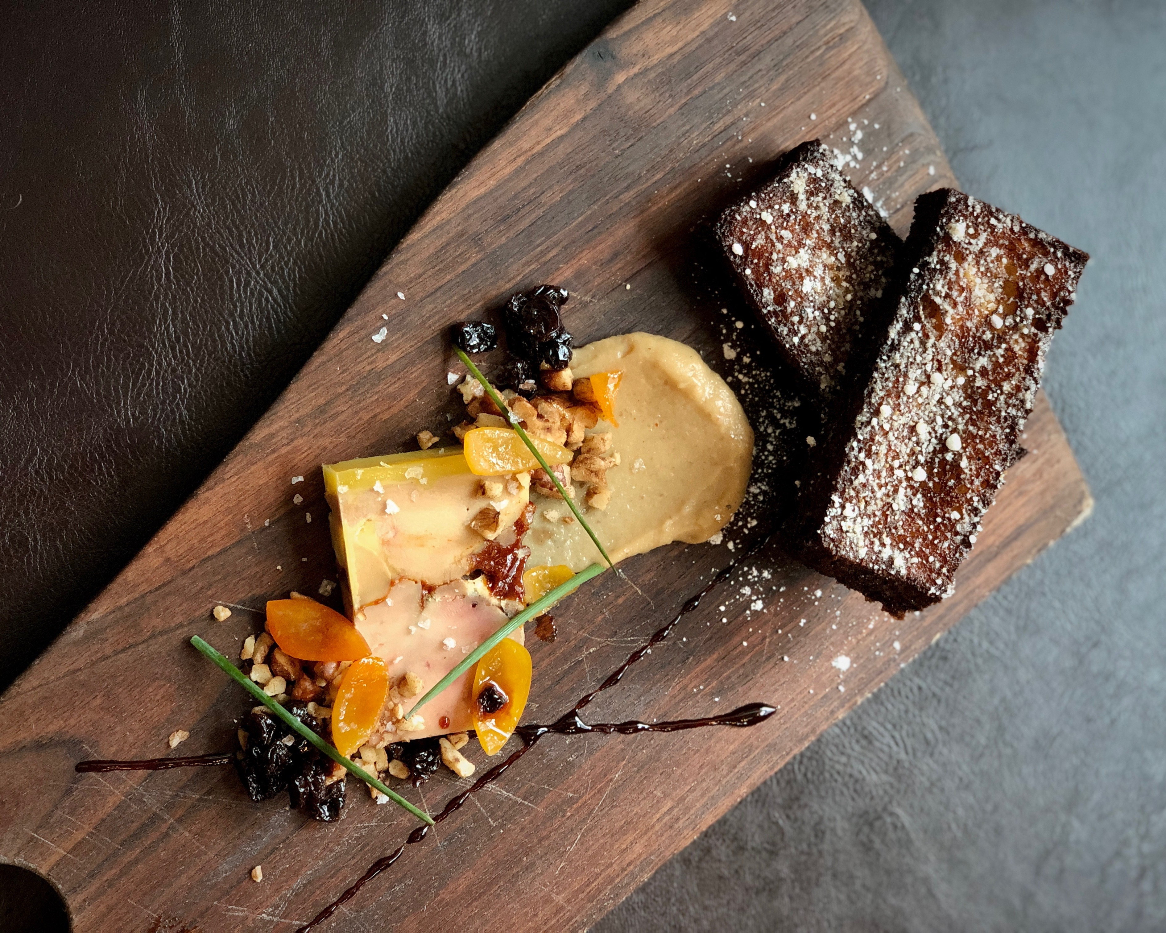Foie gras torchon is plated on a wooden board and garnished with flowers at Le Pigeon