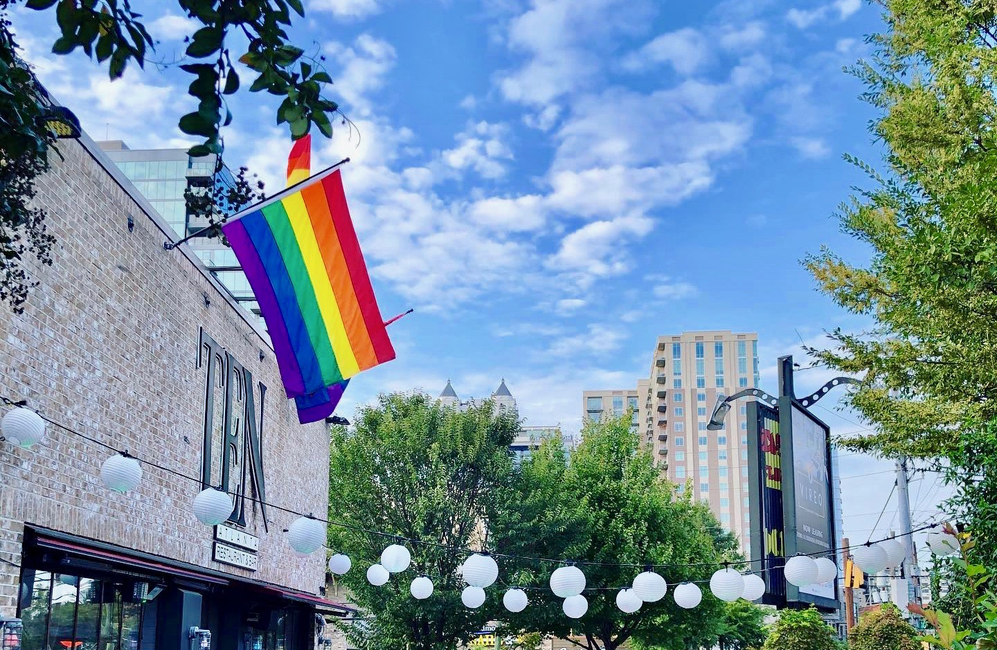 The patio and outside entrance of Ten in Midtown with two rainbow pride flags